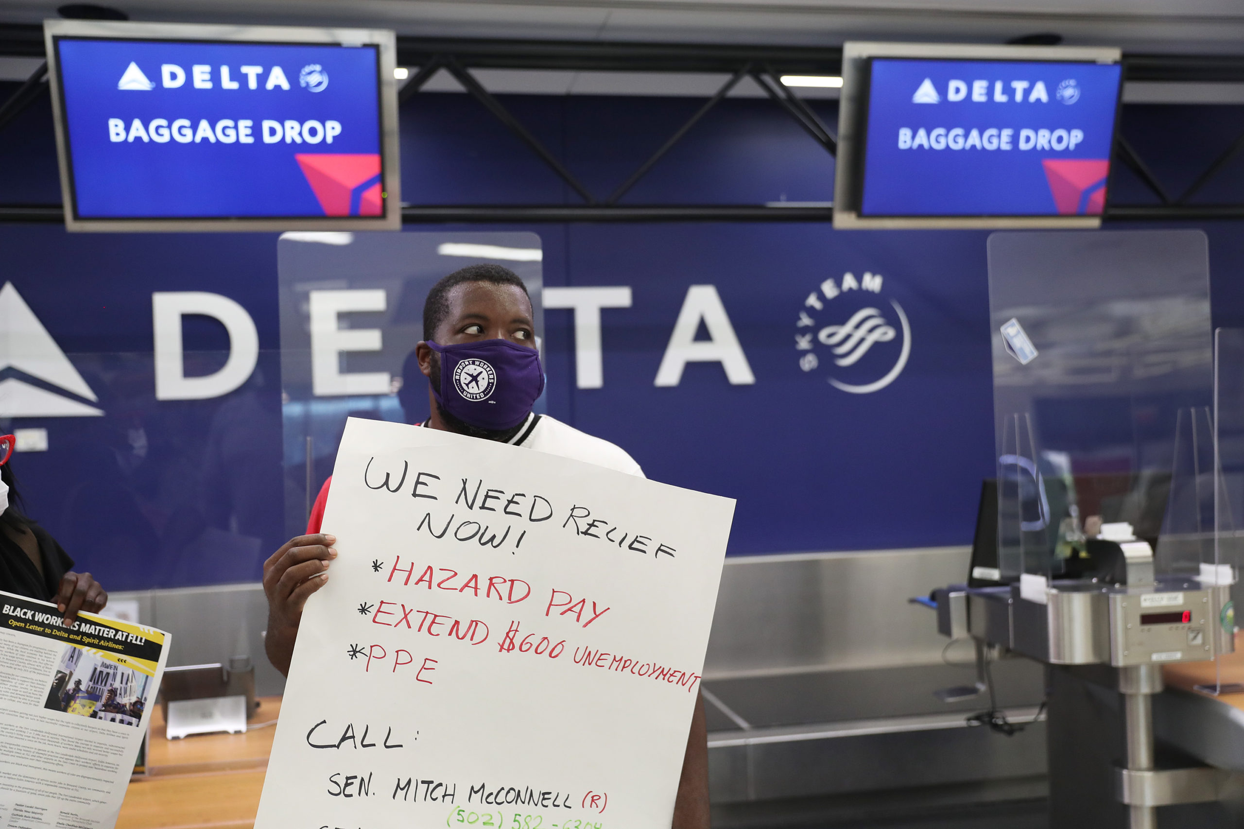 Rashad Grant joins with unemployed airport workers, the Black Lives Matter Alliance of Broward and other supporters to ask that Delta Airlines contractor, Eulen America, who the demonstrators say received $25 million from the CARES Act, hire back their unemployed Fort Lauderdale-Hollywood International Airport workers on August 13, 2020 in Fort Lauderdale, Florida. They are also asking that U.S. Senators pass the HEROES Act that provides PPE, essential pay and extended unemployment benefits for essential workers. (Photo by Joe Raedle/Getty Images)