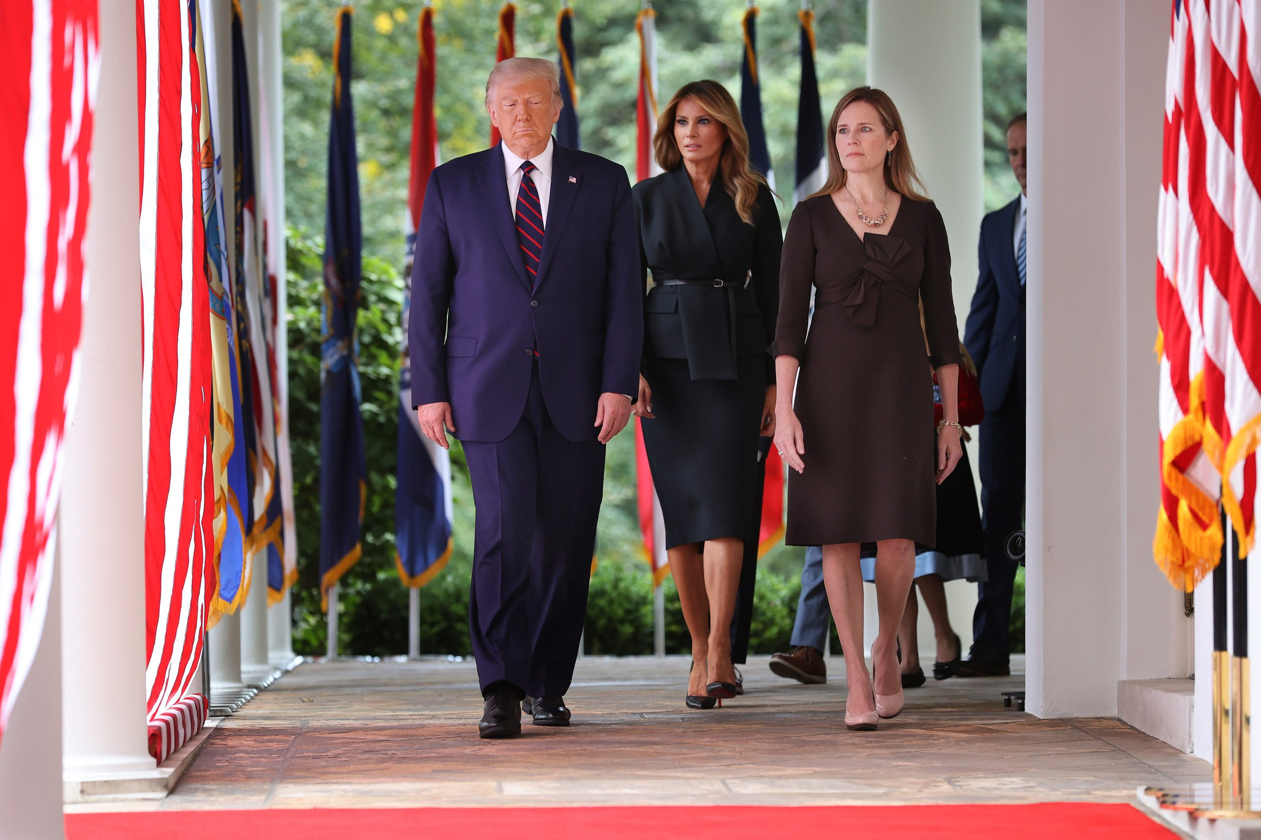 WASHINGTON, DC - SEPTEMBER 26: (L-R) President Donald Trump, first lady Melania Trump and 7th U.S. Circuit Court Judge Amy Coney Barrett, 48, walk into the Rose Garden before Trump announces Barrett as his nominee to the Supreme Court at the White House September 26, 2020 in Washington, DC. With 38 days until the election, Trump tapped Barrett to be his third Supreme Court nominee in just four years and to replace the late Associate Justice Ruth Bader Ginsburg, who will be buried at Arlington National Cemetery on Tuesday. (Photo by Chip Somodevilla/Getty Images)