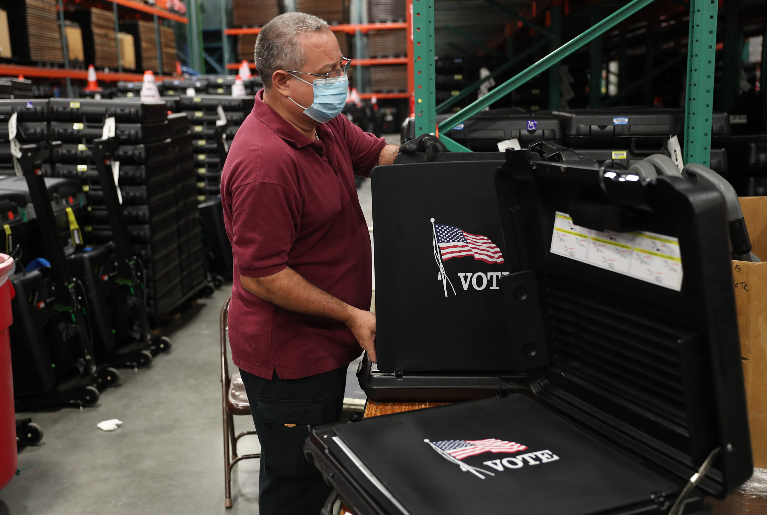 DORAL, FLORIDA - OCTOBER 01: A worker at the Miami-Dade County Election Department prepares a voting booth to be used in the general election on October 01, 2020 in Doral, Florida. The Miami-Dade County Elections Department mailed out via the U.S. Post Office more than 530,000 vote-by-mail ballots to voters with a request on file for the November 3, 2020 General Election. (Photo by Joe Raedle/Getty Images)