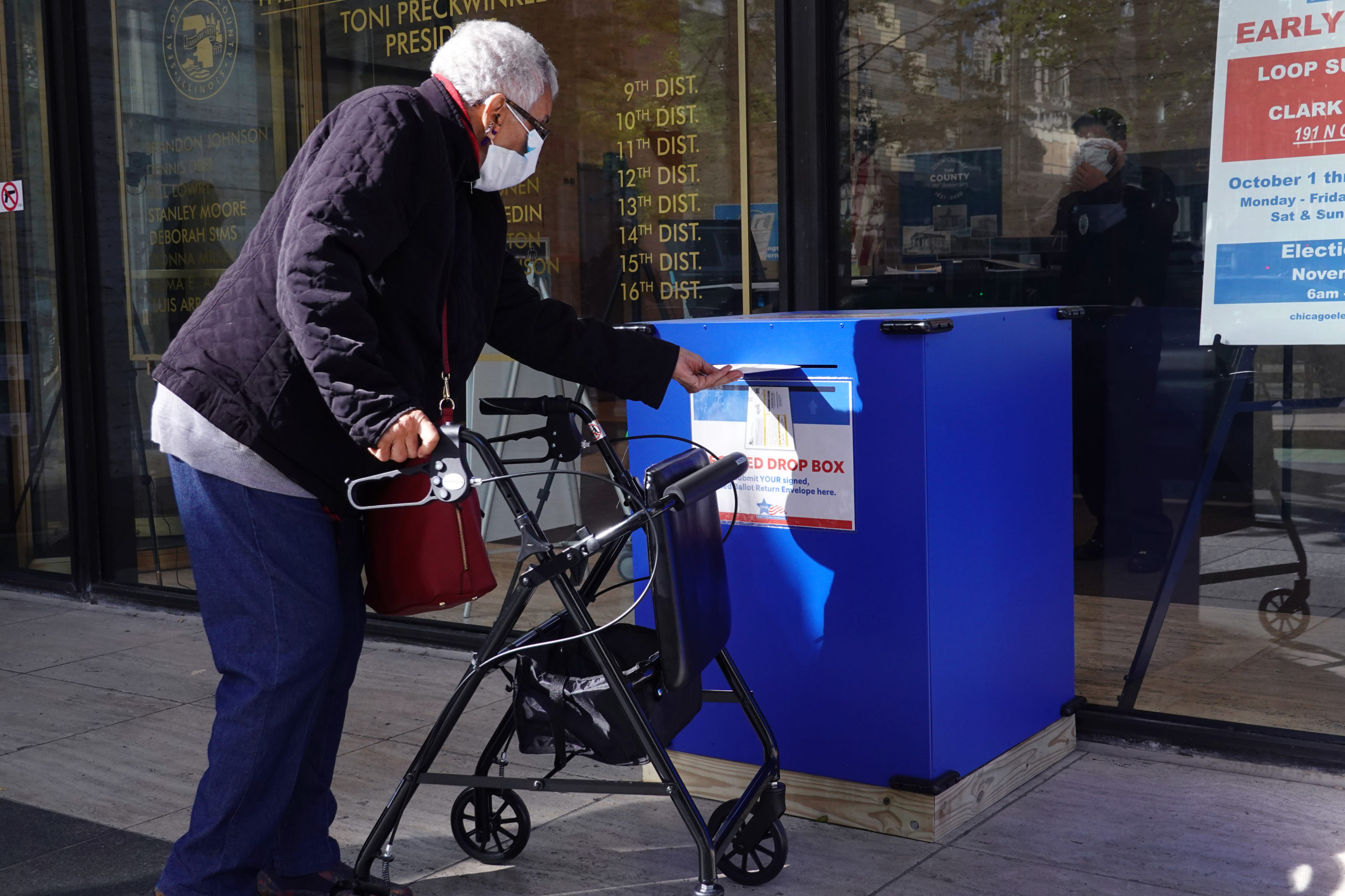 A resident drops off a mail ballot in a secure drop box on Oct. 02 in Chicago, Illinois. (Scott Olson/Getty Images)