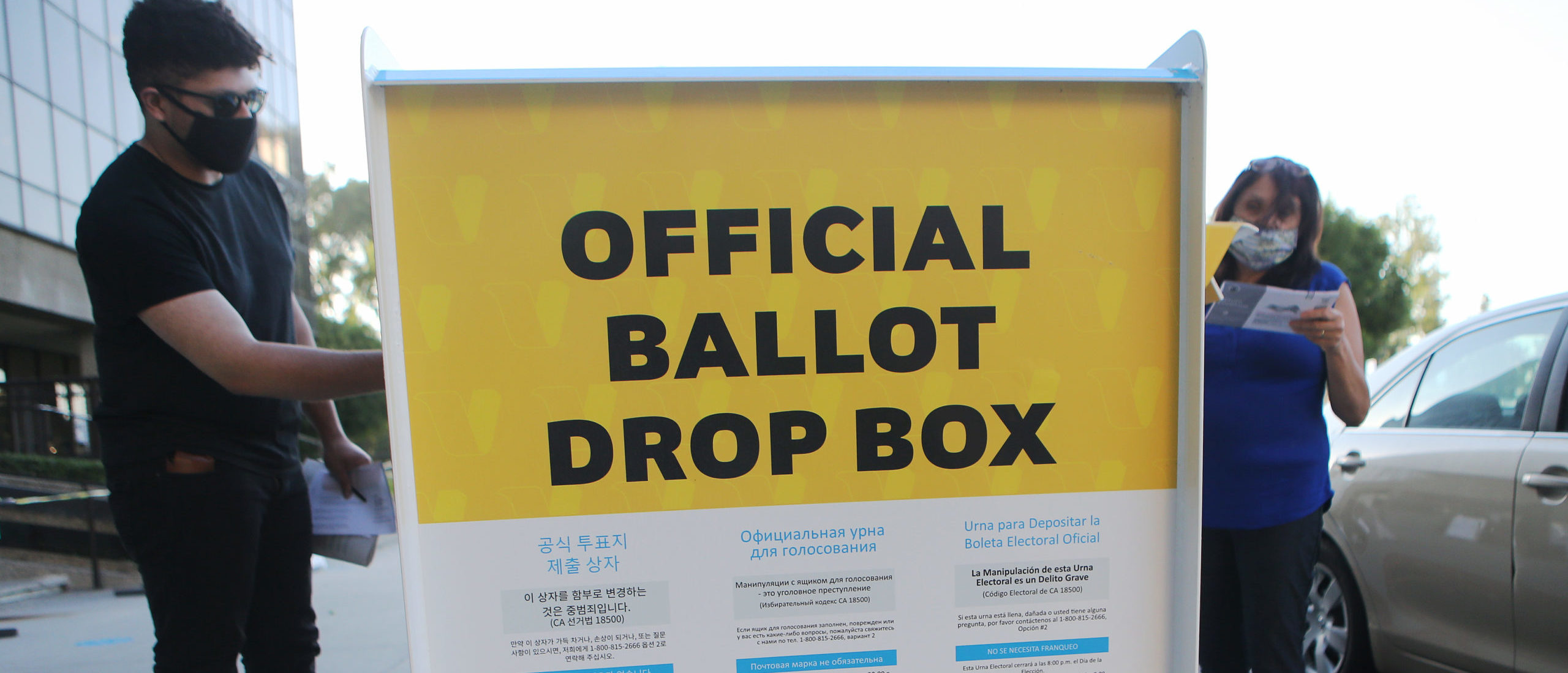 Pedestrians place ballots in an official mail-in ballot drop box outside of the L.A. County Registrar's office ahead of Election Day on October 14, 2020. (Photo by Mario Tama/Getty Images)