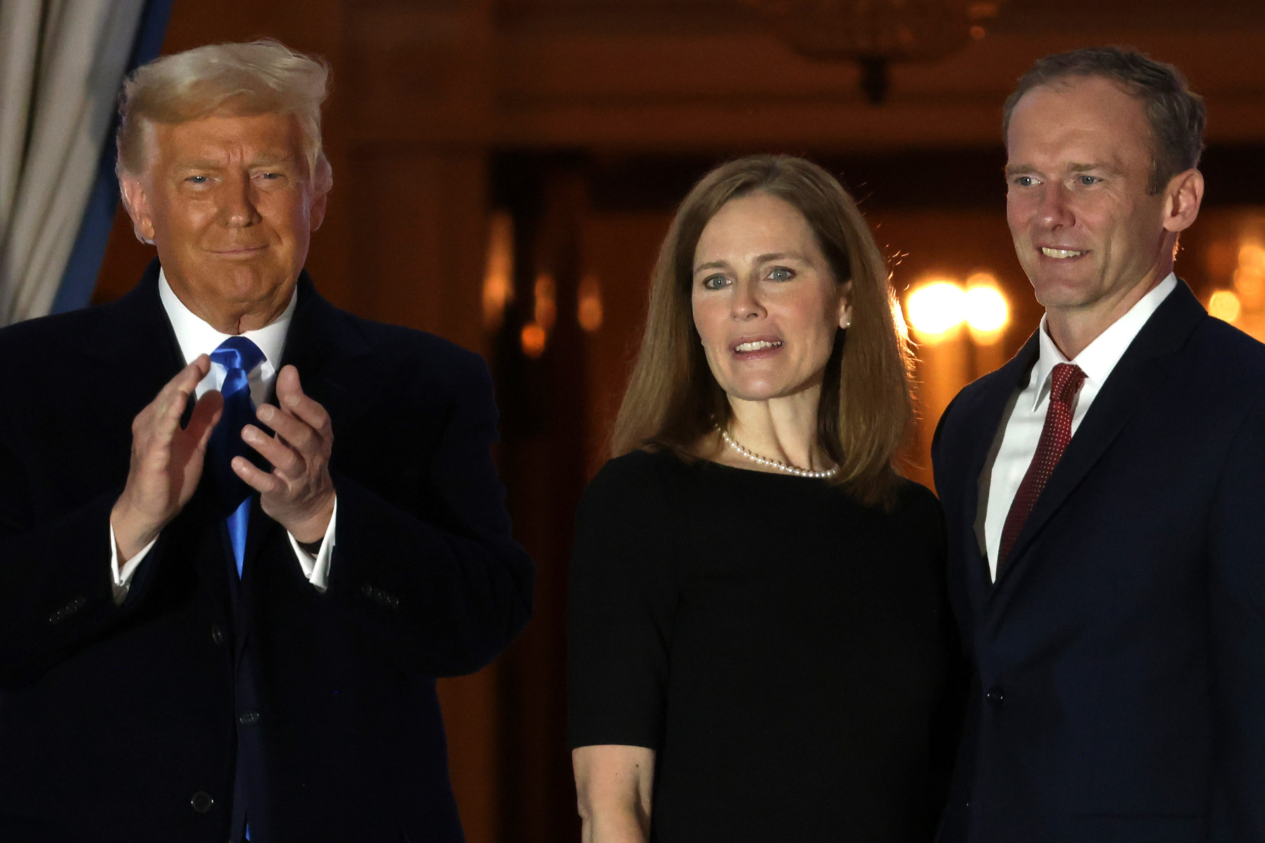 WASHINGTON, DC - OCTOBER 26: (L-R) U.S. President Donald Trump, newly sworn-in U.S. Supreme Court Associate Justice Amy Coney Barrett and her husband Jesse Barrett look on during a ceremonial swearing-in on the South Lawn of the White House October 26, 2020 in Washington, DC. The Senate confirmed Barrett's nomination to the Supreme Court today by a vote of 52-48. (Photo by Alex Wong/Getty Images)