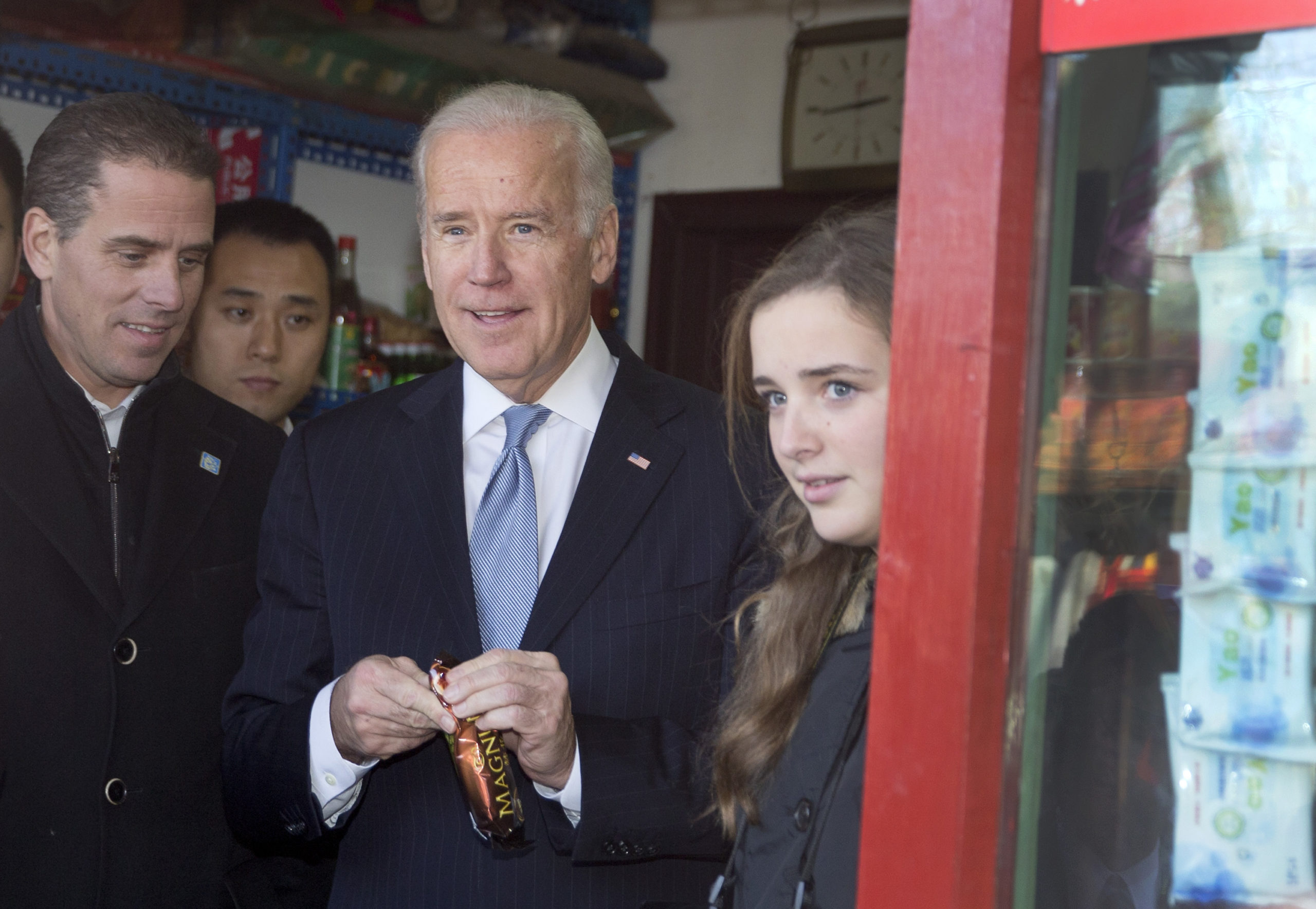 U.S. Vice President Joe Biden, center, buys an ice-cream at a shop as he tours a Hutong alley with his granddaughter Finnegan Biden, right, and son Hunter Biden, left on December 5, 2013 in Beijing, China. (Andy Wong-Pool/Getty Images)