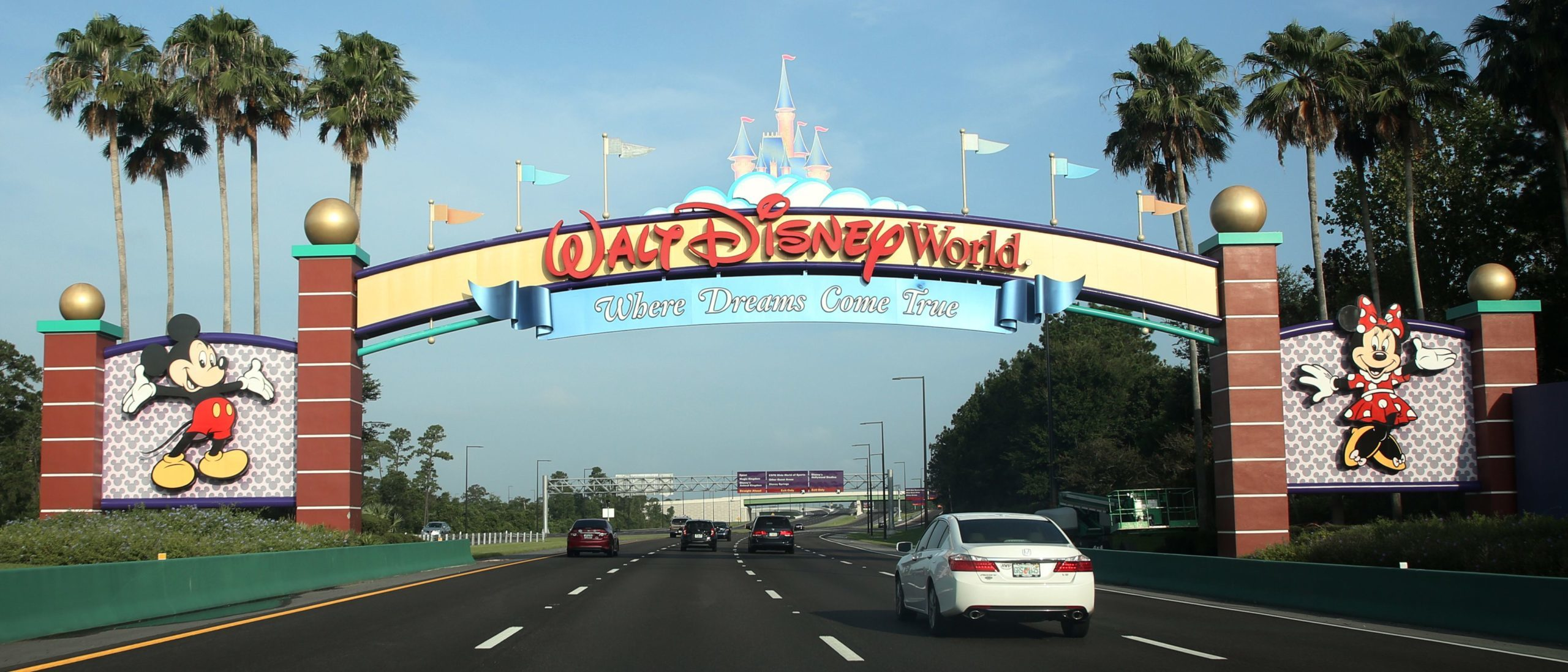 Visitors drive past a sign welcoming them to Walt Disney World on the first day of reopening of the iconic Magic Kingdom. (Photo by GREGG NEWTON/Gregg Newton/AFP via Getty Images)