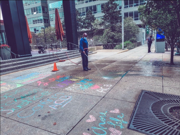 A building staff member hoses down Students for Life of America group's sidewalk chalk statements supporting Amy Coney Barrett on Oct. 23. (Kevin Feliciano / Students for Life of America)