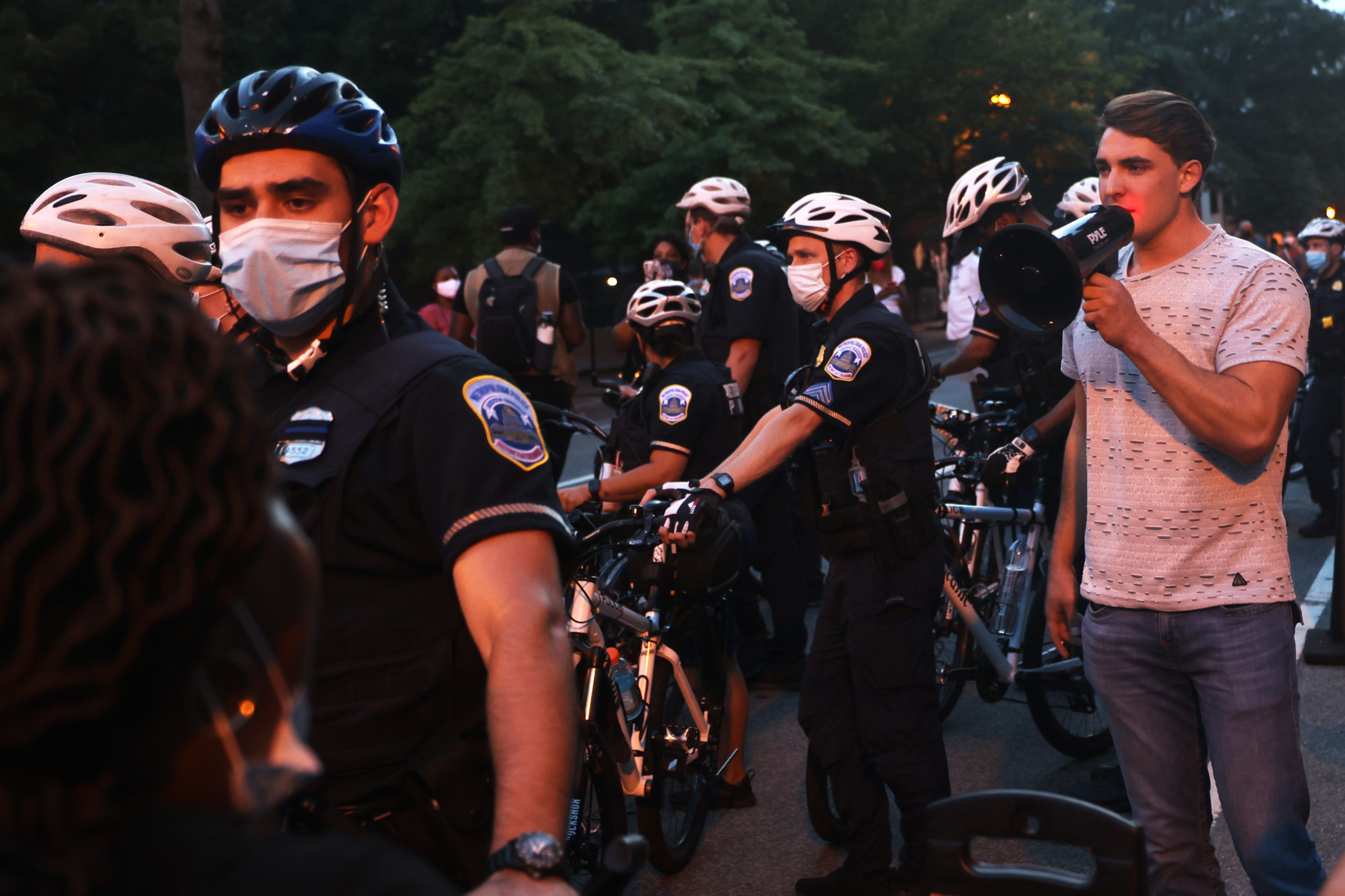 """WASHINGTON, DC - AUGUST 27: Police officers surround Jacob Wohl as he taunts protesters during a """"Trump/Pence Out Now"""" rally at Black Lives Matter plaza August 27, 2020 in Washington, DC. Protesters gathered as the Republican National Convention on its final night was set to nominate President Donald Trump for a second term in office. (Photo by Michael M. Santiago/Getty Images)"""