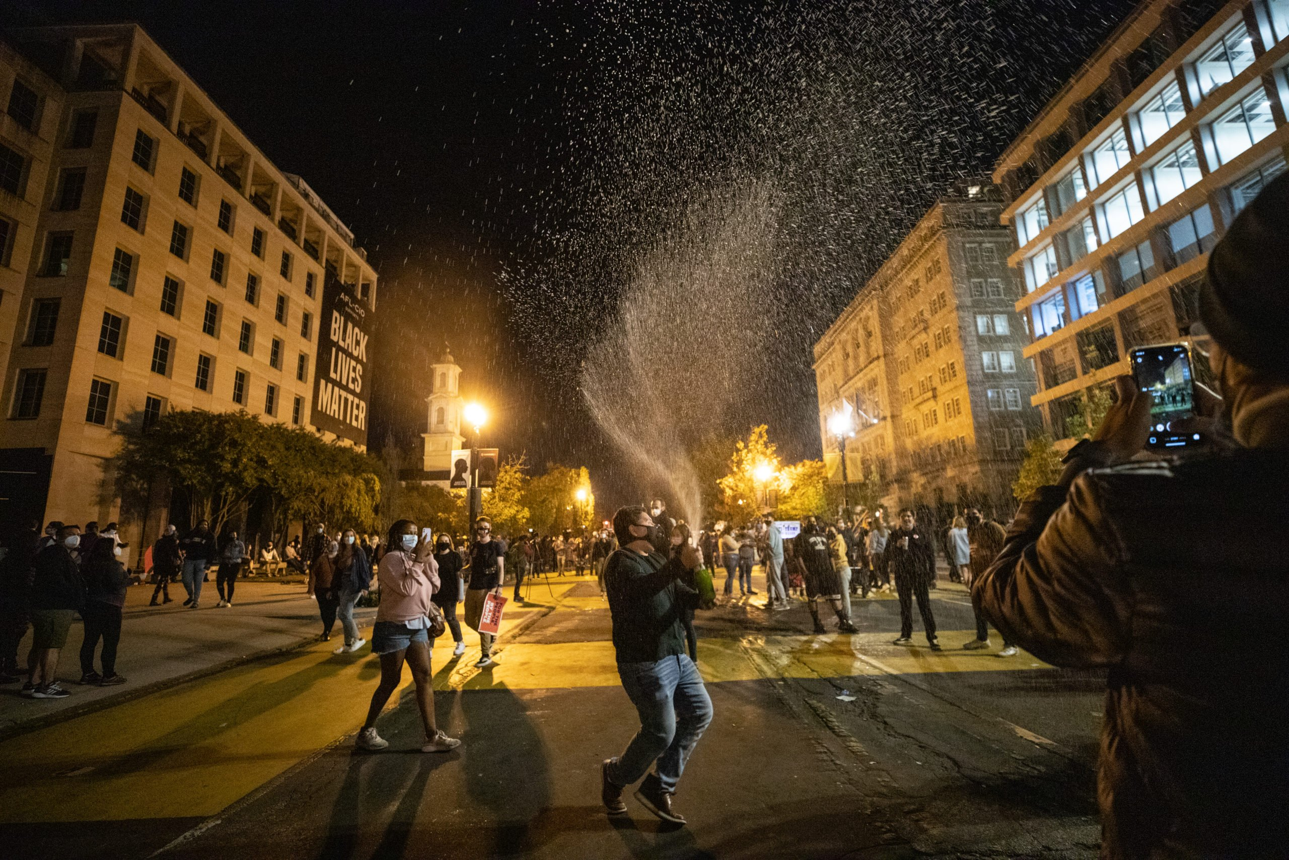 People gathered at Black Lives Matter Plaza on Saturday night to pop bottles of champagne in celebration of the predicted election of Democratic nominee Joe Biden and Kamala Harris, in Washington D.C. on Nov. 7, 2020. (Kaylee Greenlee - Daily Caller News Foundation)
