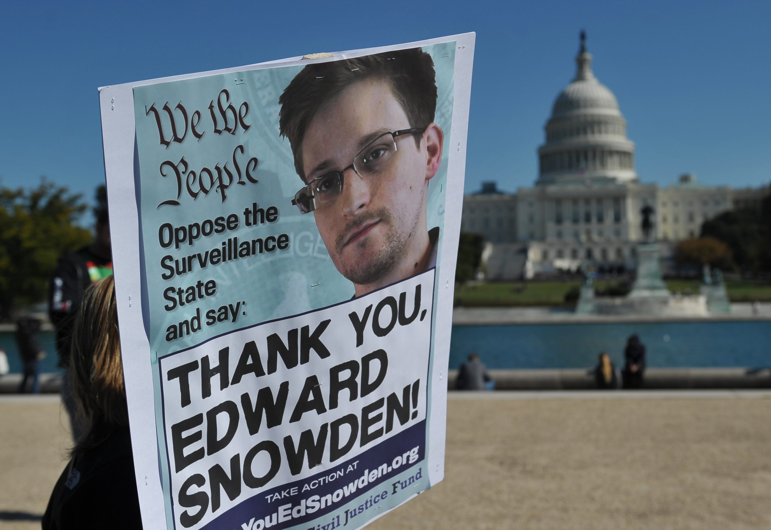 Demonstrators hold placards supporting former US intelligence analyst Edward Snowden during a protest against government surveillance on October 26, 2013 in Washington, DC. (MANDEL NGAN/AFP via Getty Images)