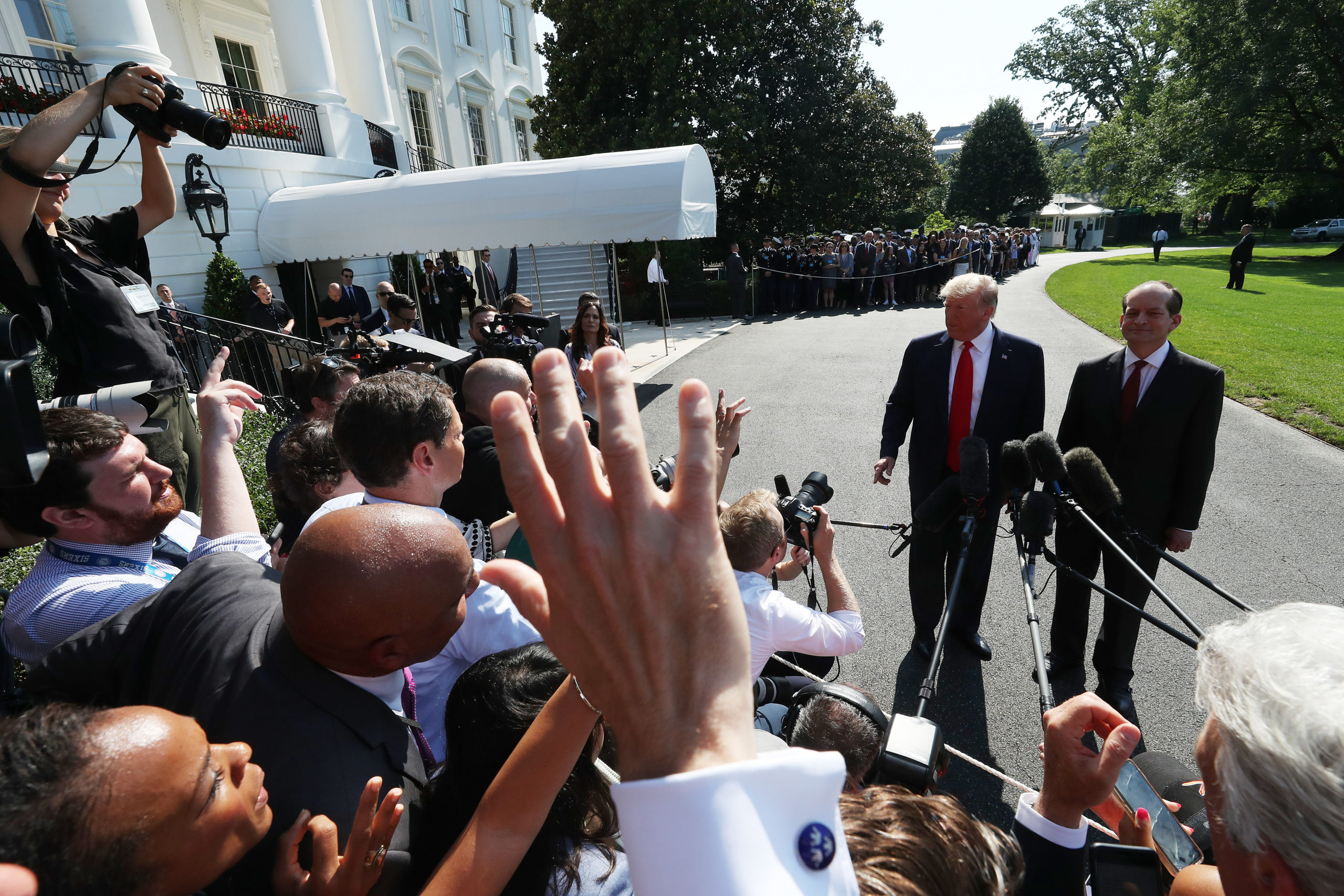 U.S. President Donald Trump stands with Labor Secretary Alex Acosta, who announced his resignation, while talking to the media at the White House on July 12, 2019 in Washington, DC. Acosta has been under fire for his role in the Jeffrey Epstein plea deal over a decade ago when he was a U.S. Attorney in Florida. (Mark Wilson/Getty Images)