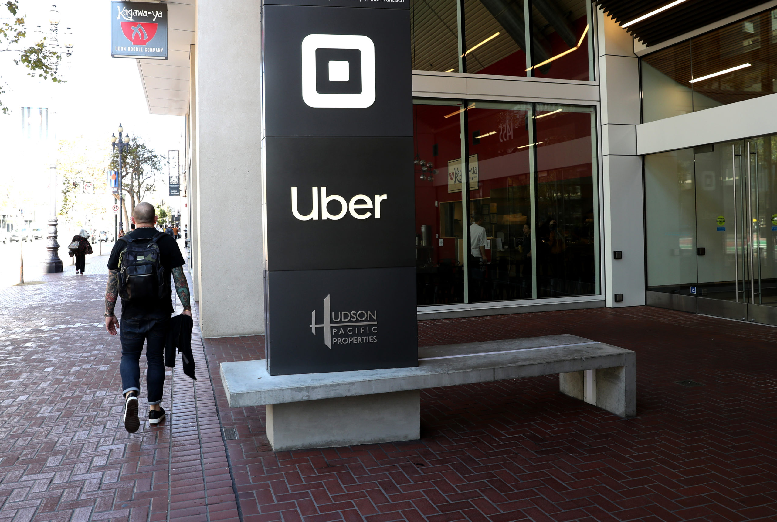 A pedestrian walks by Uber headquarters in San Francisco, California. (Justin Sullivan/Getty Images)