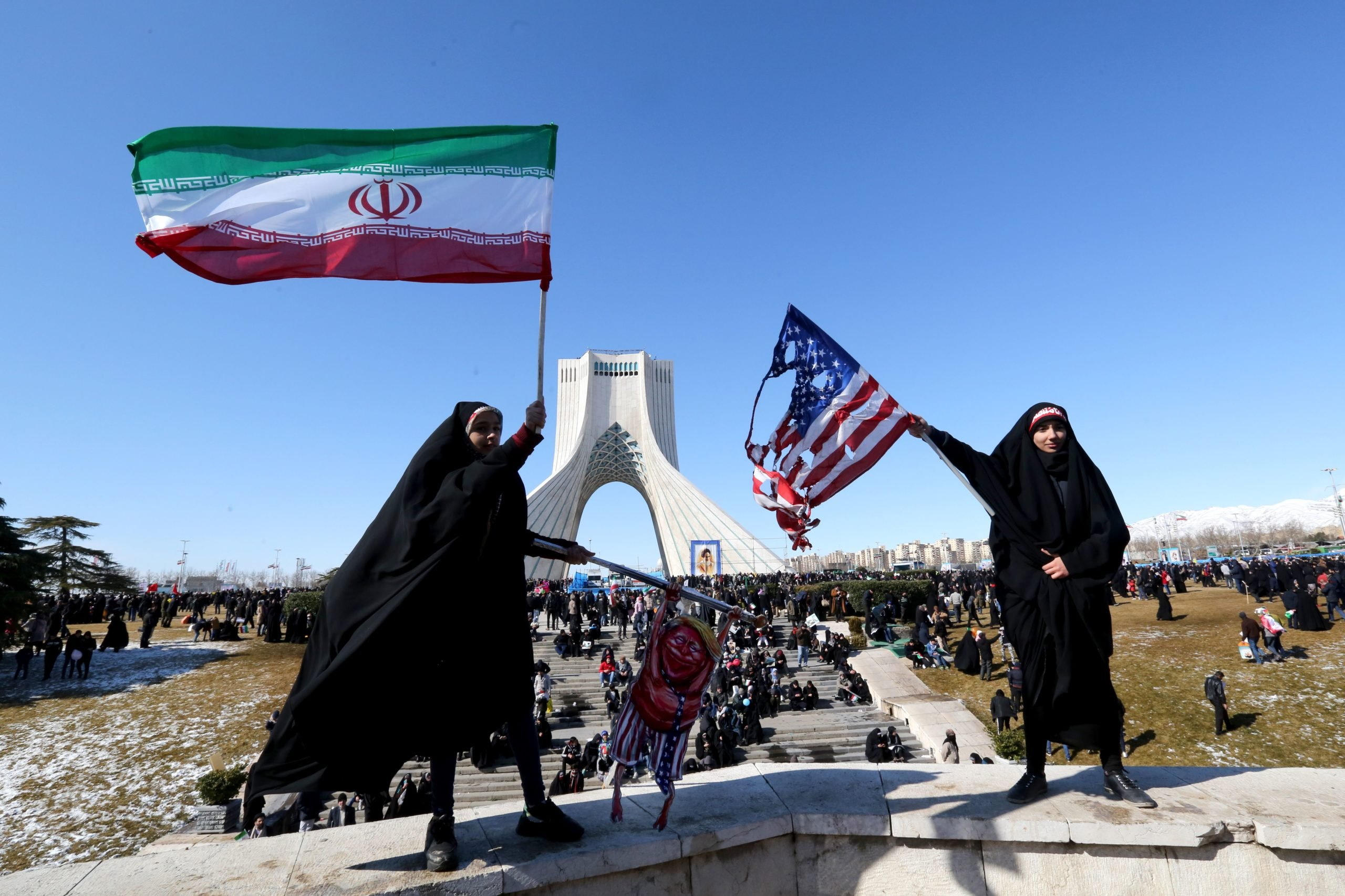 Iranian women wave a national flag (L) and a burnt US flag (R) during commemorations marking 41 years since the Islamic Revolution in the capital Tehran's Azadi Square on February 11, 2020. - Thousands of Iranians massed for commemorations marking 41 years since the Islamic Revolution, in a show of unity at a time of heightened tensions with the United States. The celebrations mark the day that Shiite cleric Khomeini returned from exile and ousted the shah's last government. (Photo by ATTA KENARE/AFP via Getty Images)
