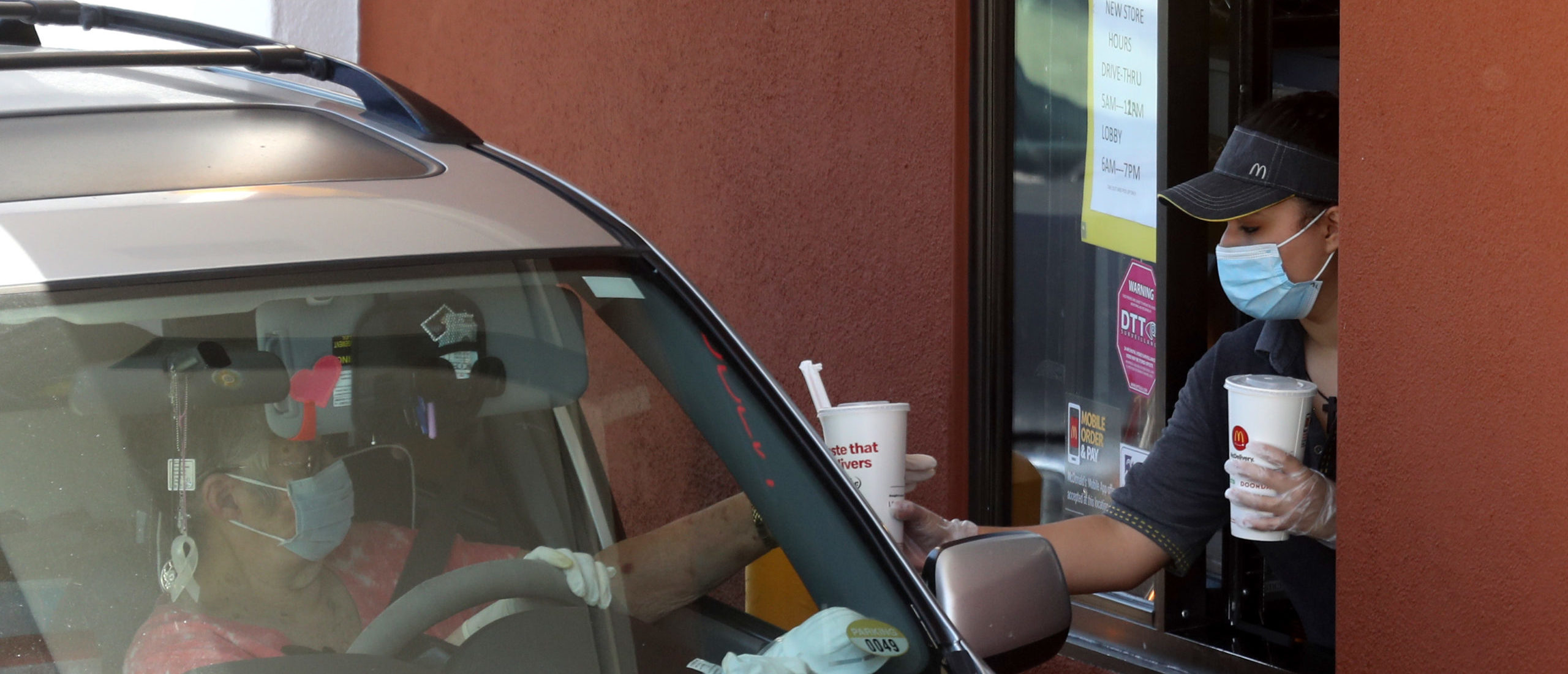 A worker wears a mask and gloves as she hands soft drinks to a customer at a McDonald's drive-thru on April 22, 2020 in Novato, California. (Photo by Justin Sullivan/Getty Images)