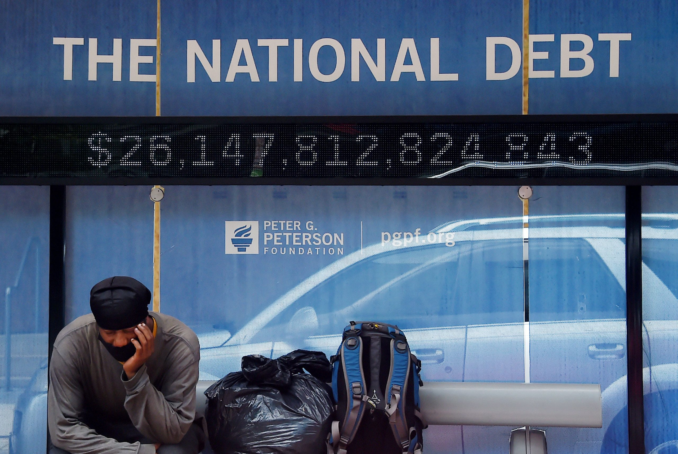 A man waits at a bus stop that displays the national debt of the United States on June 19 in Washington, D.C. (Olivier Douliery/AFP via Getty Images)