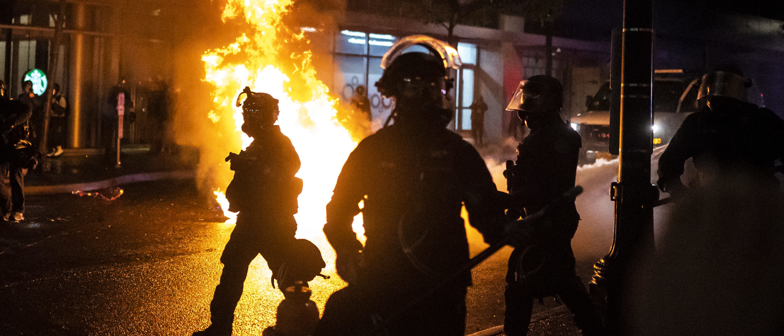 PORTLAND, OR - SEPTEMBER 23: Portland police walk past a fire started by a Molotov cocktail thrown at police on September 23, 2020 in Portland, United States. Violent protests erupted across the nation Wednesday following the results of a grand jury investigation into the police shooting death of Breonna Taylor. (Photo by Nathan Howard/Getty Images)