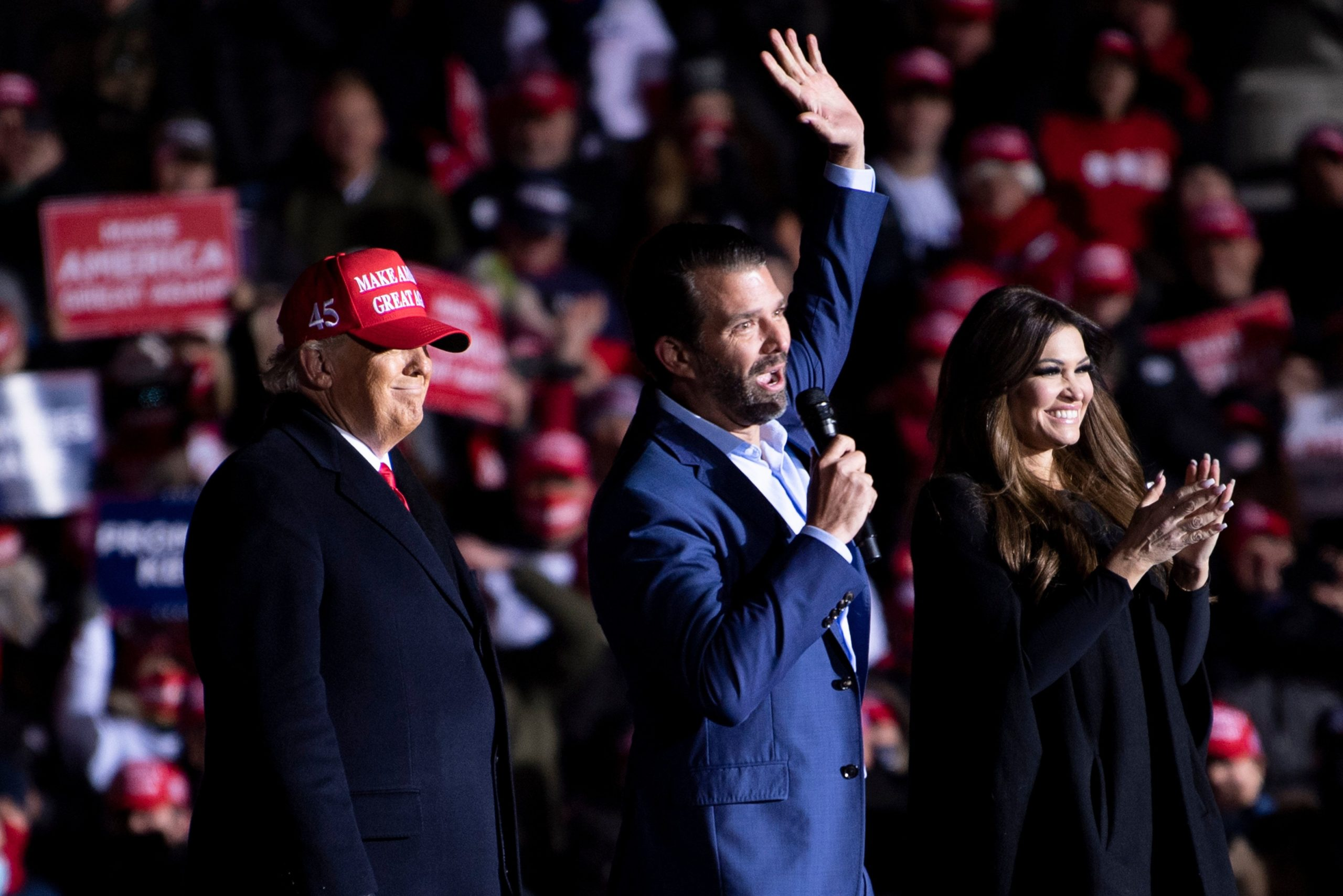 US President Donald Trump and Kimberly Guilfoyle listen while Donald Trump Jr. speaks during a Make America Great Again rally at Kenosha Regional Airport November 2, 2020, in Kenosha, Wisconsin. (Photo by BRENDAN SMIALOWSKI/AFP via Getty Images)
