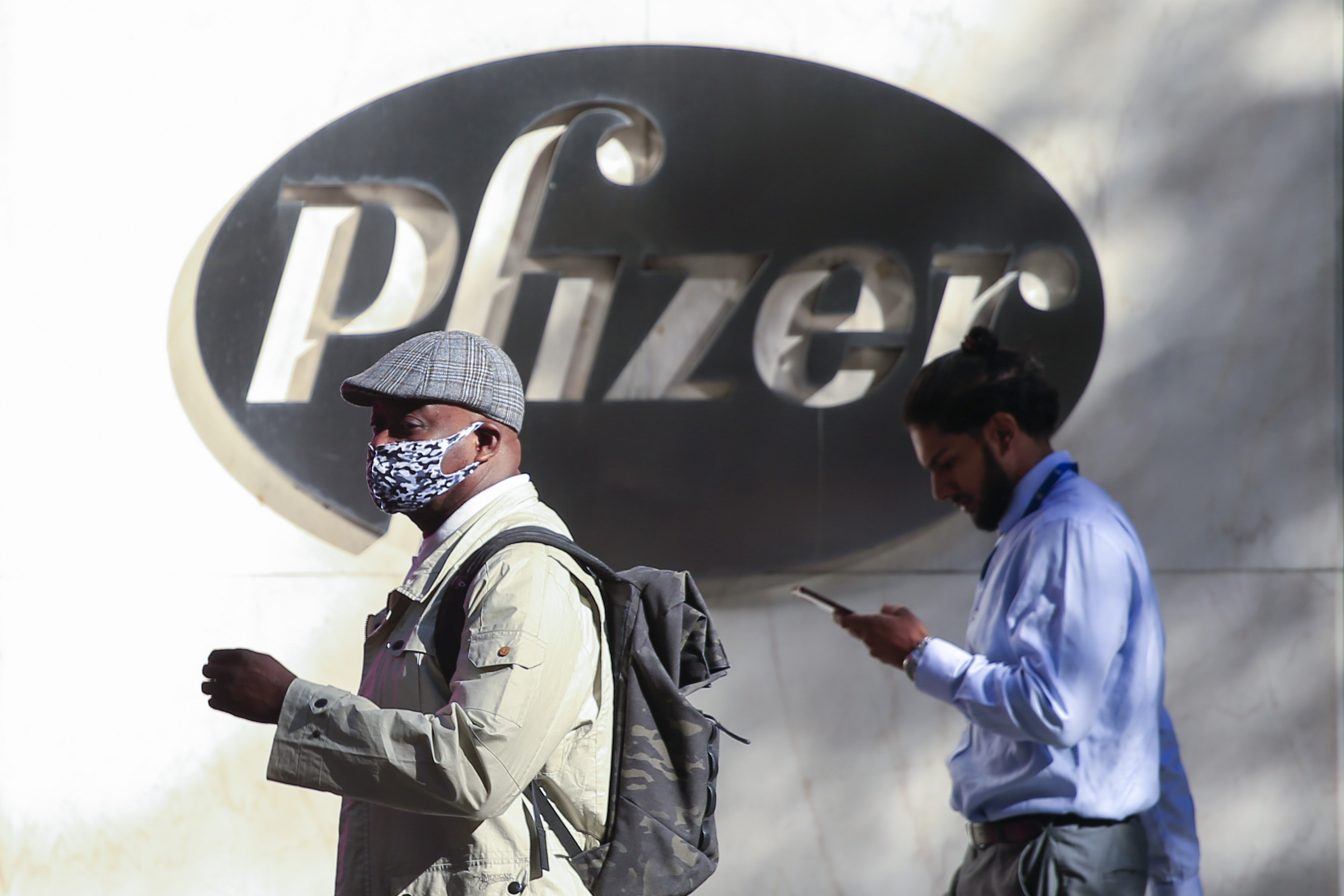 People walk by the Pfizer world headquarters in New York on Nov. 9. (Kena Betancur/AFP via Getty Images)