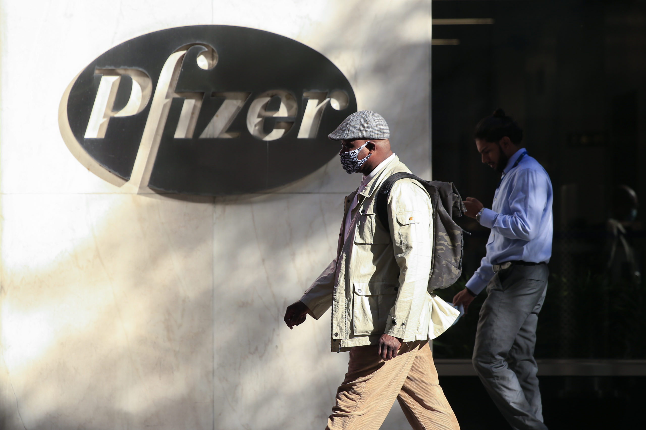 People walk by the Pfizer world headquarters in New York on Monday. (Kena Betancur/AFP via Getty Images)