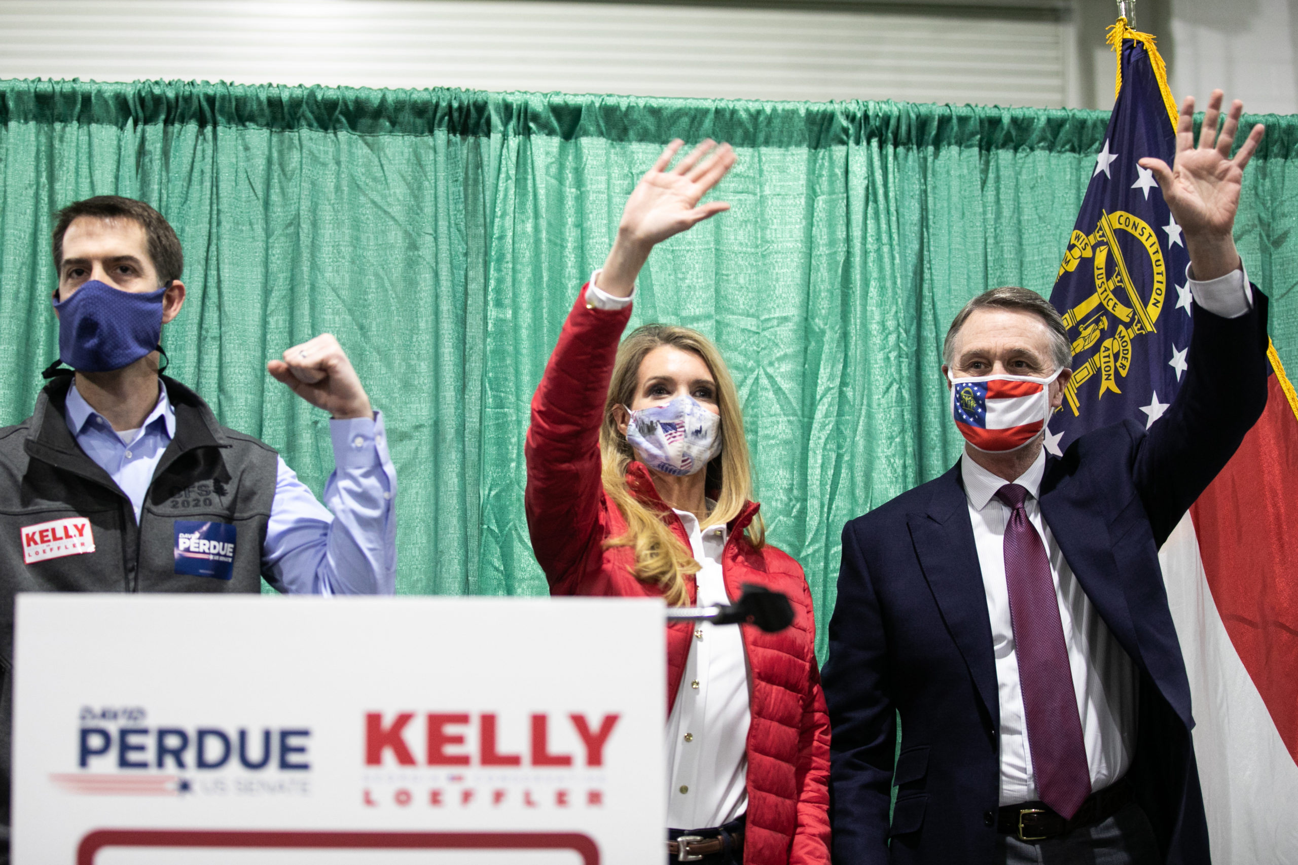 """U.S. Sen. David Purdue (R-GA) and Sen. Kelly Loeffler (R-GA) wave to the crowd of supporters at a """"Defend the Majority"""" rally with Sen. Tom Cotton (R-AR) at the Georgia National Fairgrounds and Agriculture Center on November 19, 2020 in Perry, Georgia. (Jessica McGowan/Getty Images)"""
