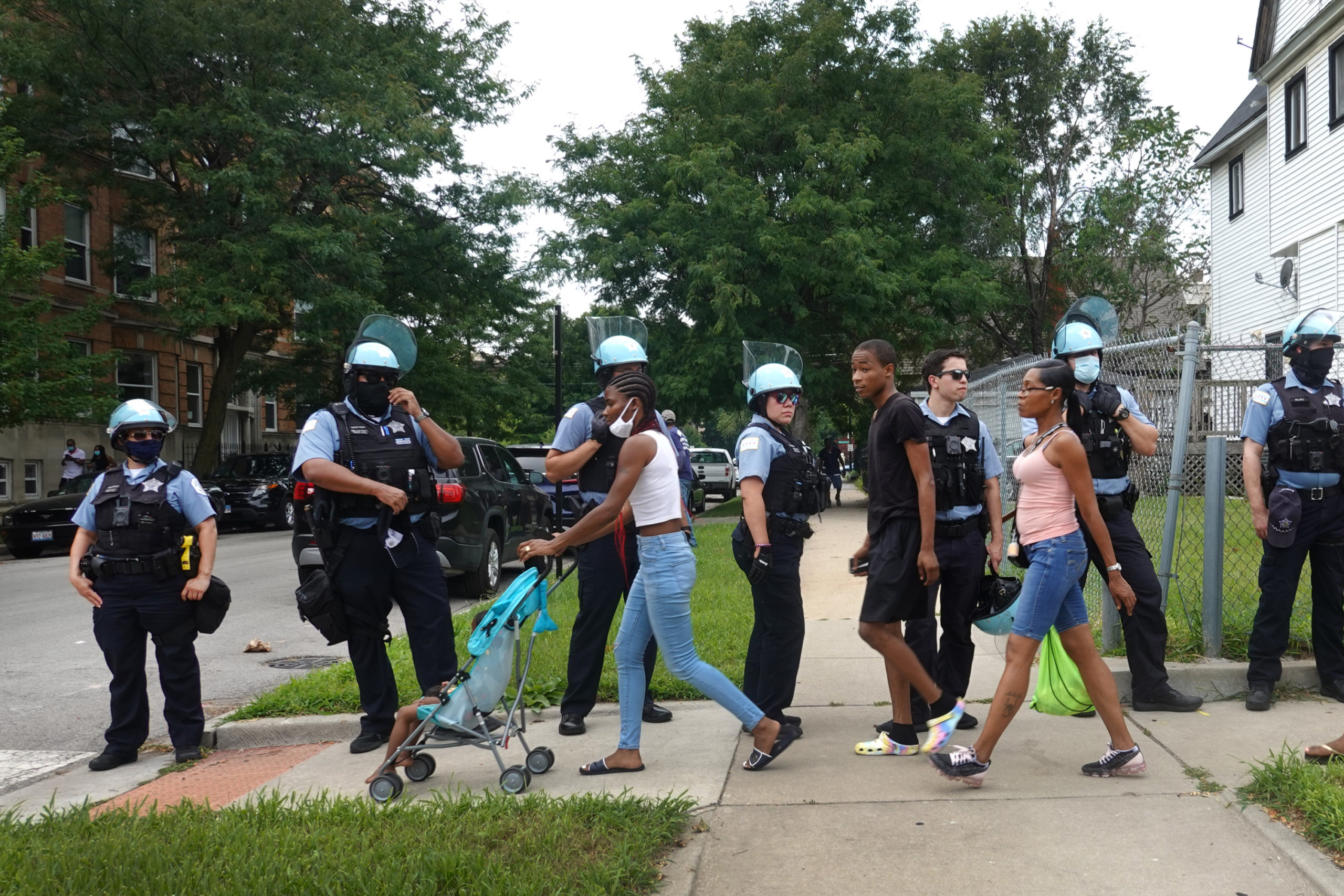 CHICAGO, ILLINOIS - AUGUST 15: Residents walk past police as they shadow demonstrators protesting police brutality as they march toward downtown on August 15, 2020 in Chicago, Illinois. The demonstration was one of several in the city today, either in support of or in opposition to police. (Scott Olson/Getty Images)