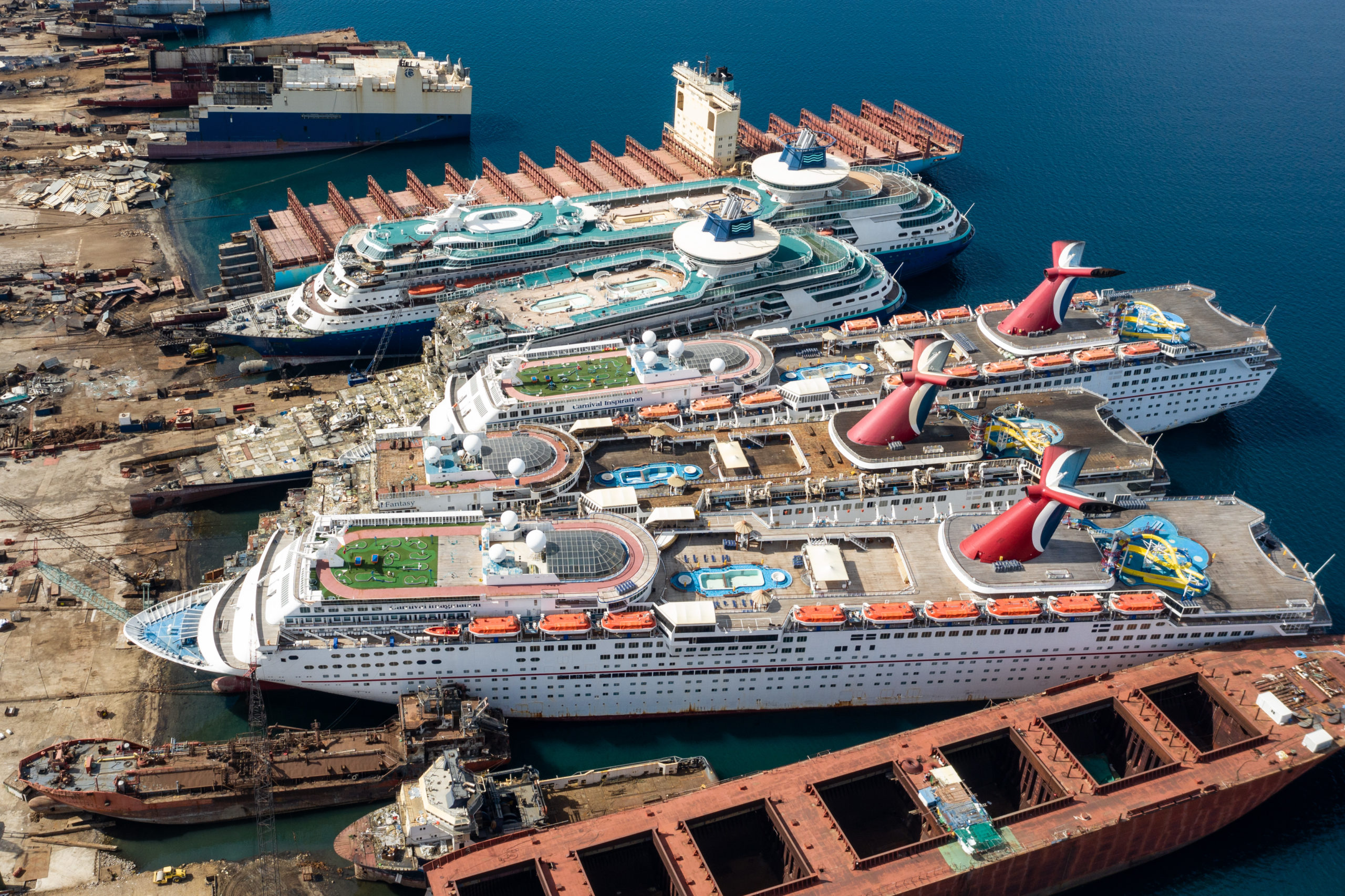 IZMIR, TURKEY - OCTOBER 02: In this aerial view from a drone, five luxury cruise ships are seen being broken down for scrap metal at the Aliaga ship recycling port on October 02, 2020 in Izmir, Turkey. With the global coronavirus pandemic pushing the multi-billion dollar cruise industry into crisis, some cruise operators have been forced to cut losses and retire ships earlier than planned. The cruise industry has been one of the hardest hit industries with public confidence in cruise holidays plummeting after a series of outbreaks occurred on cruise liners as the pandemic spread. The crisis however has bolstered the years intake of ships at the Aliaga ship recycling port with business up thirty percent on the previous year. (Photo by Chris McGrath/Getty Images)