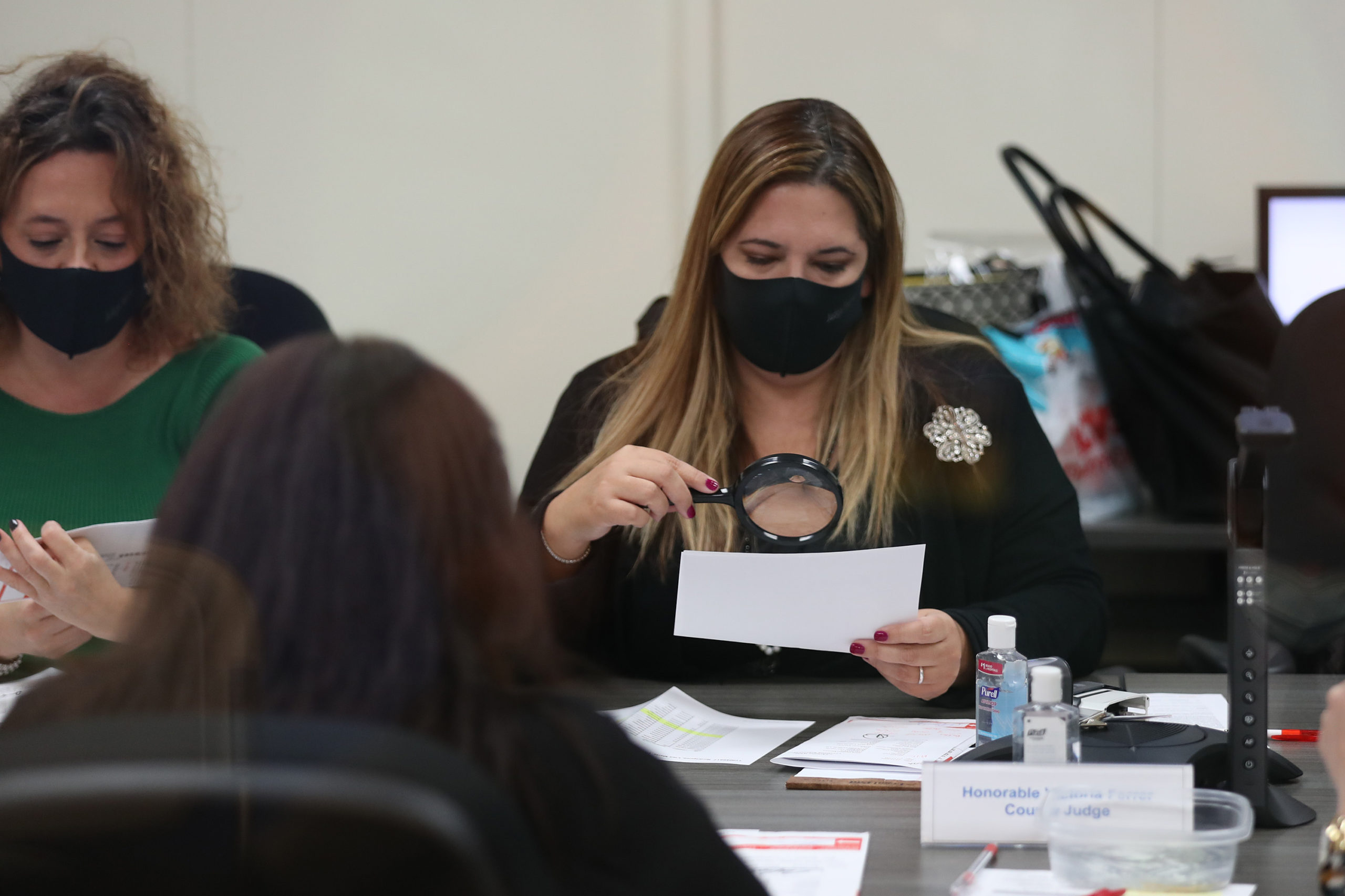 Victoria Ferrer, County Judge, working with the Miami-Dade County Canvassing Board uses a magnifying glass to inspect a Vote-by-Mail ballot for a valid signature at the Miami-Dade County Elections Department on Nov. 3. (Joe Raedle/Getty Images)