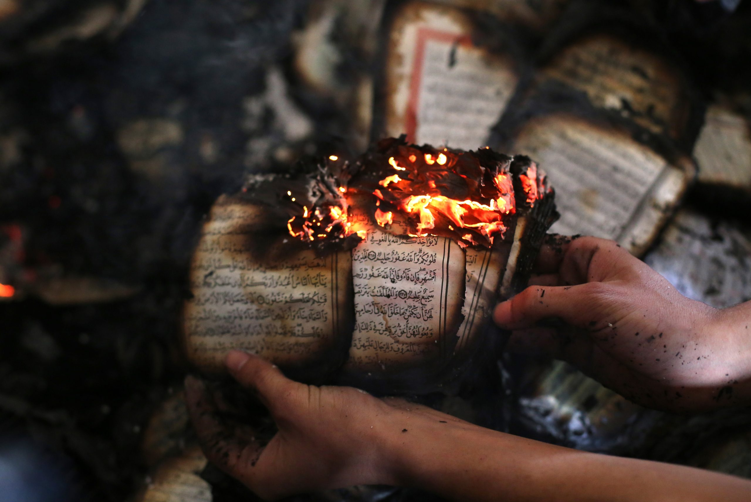 A Palestinian man displays a copy of Islam's holy book, the Koran, still burning inside a mosque that was set ablaze by Israeli settlers in al-Mughayir, in the occupied West Bank near the Jewish settlement of Shilo, on November 12, 2014. Israeli settlers torched the West Bank mosque in an apparent revenge attack, after separate Palestinian knife attacks the previous day killed a settler in the southern Western Bank and an Israeli soldier in Tel Aviv. AFP PHOTO / ABBAS MOMANI (Photo credit should read ABBAS MOMANI/AFP via Getty Images)