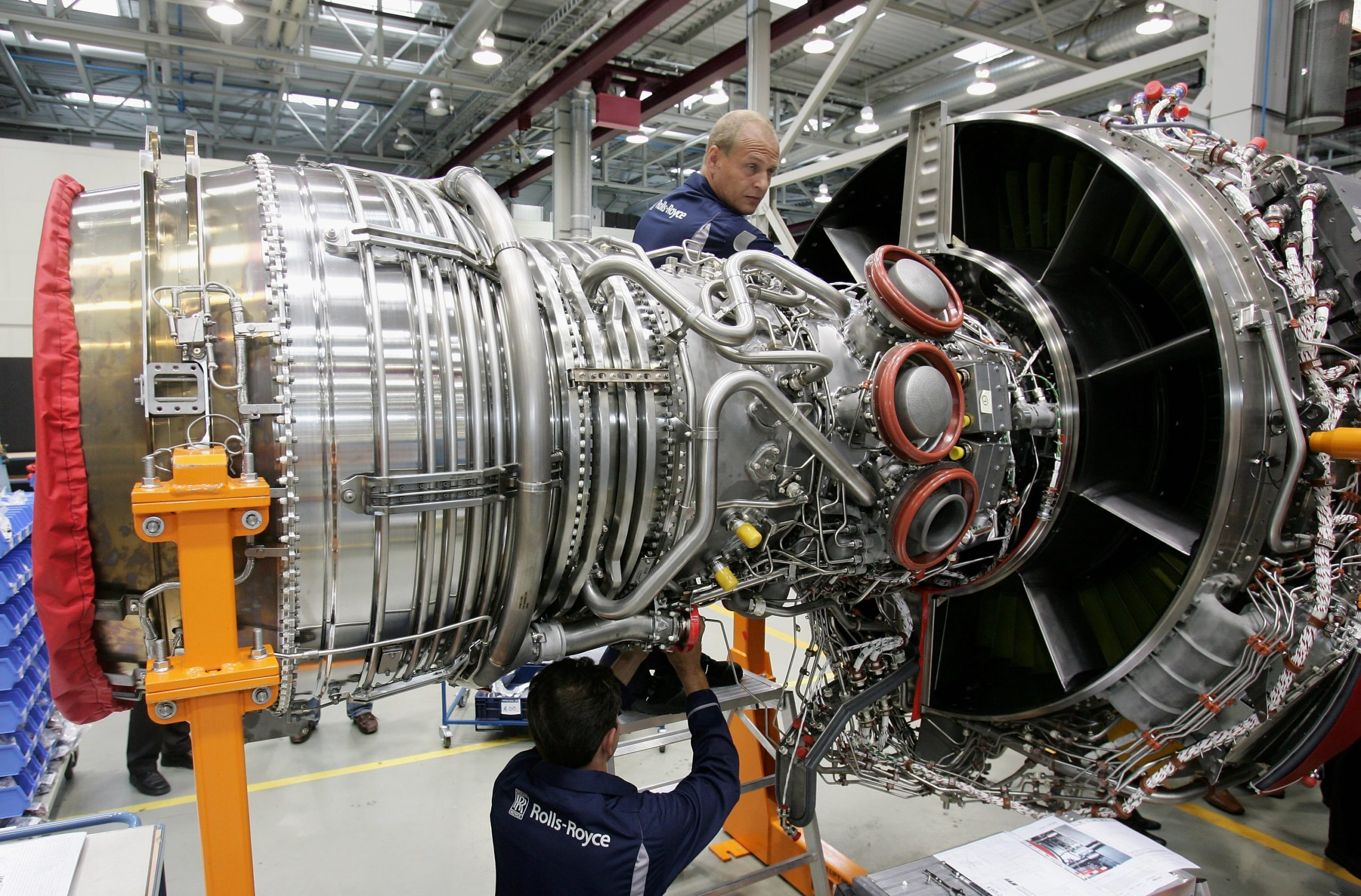 Workers assemble an aircraft jet engine August 23, 2006 at the Rolls-Royce aircraft engine factory in Berlin, Germany. The factory, a greenfield project built in 1993 in what was East Germany before 1989, produces jet engines for aircraft makers including Airbus and Boeing. The plant's production is also typical of the high-tech exports that make the Germany the world's biggest exporter. (Photo by Sean Gallup/Getty Images)