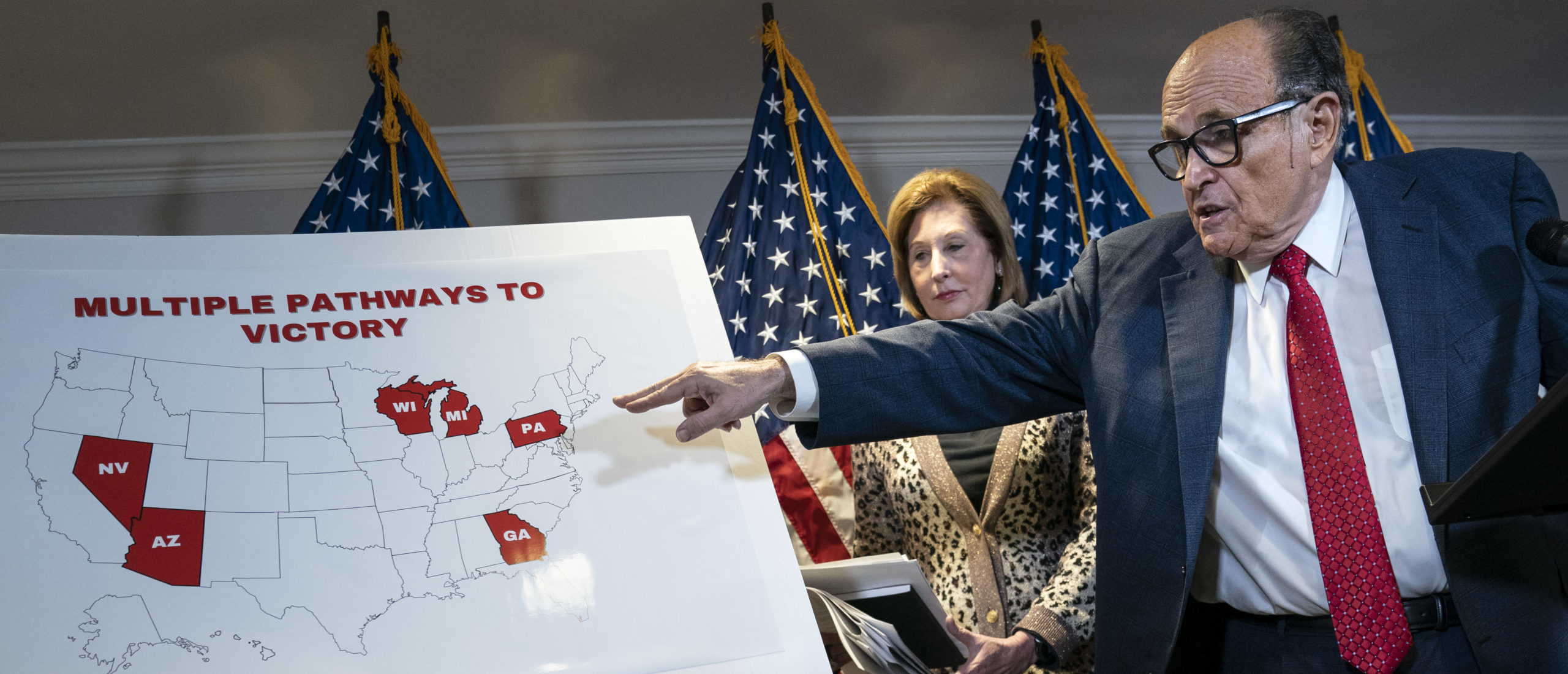 WASHINGTON, DC - NOVEMBER 19: Rudy Giuliani points to a map as he speaks to the press about various lawsuits related to the 2020 election, inside the Republican National Committee headquarters on November 19, 2020 in Washington, DC. President Donald Trump, who has not been seen publicly in several days, continues to push baseless claims about election fraud and dispute the results of the 2020 United States presidential election. Also pictured, at center, is attorney Sidney Powell. (Photo by Drew Angerer/Getty Images)