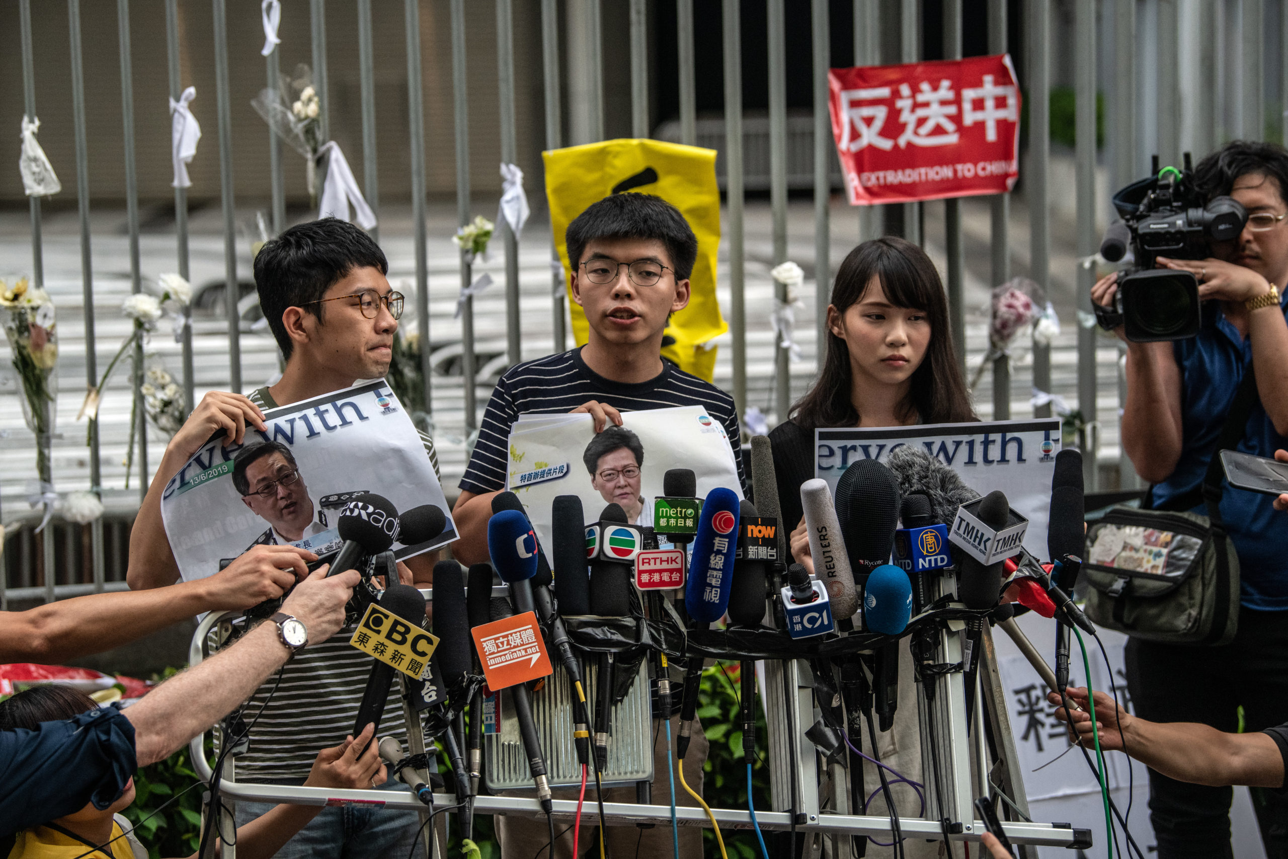 Pro-democracy activist Joshua Wong (C) speaks to members of the media outside the Legislative Council building following a press conference by Hong Kong Chief Executive Carrie Lam on June 18, 2019 in Hong Kong.