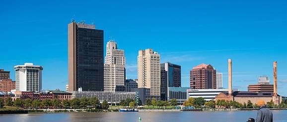 Toledo, USA - September 22, 2014: Three men fish and talk at the banks of the Maumee River with the downtown skyline in the background in Toledo, Ohio.
