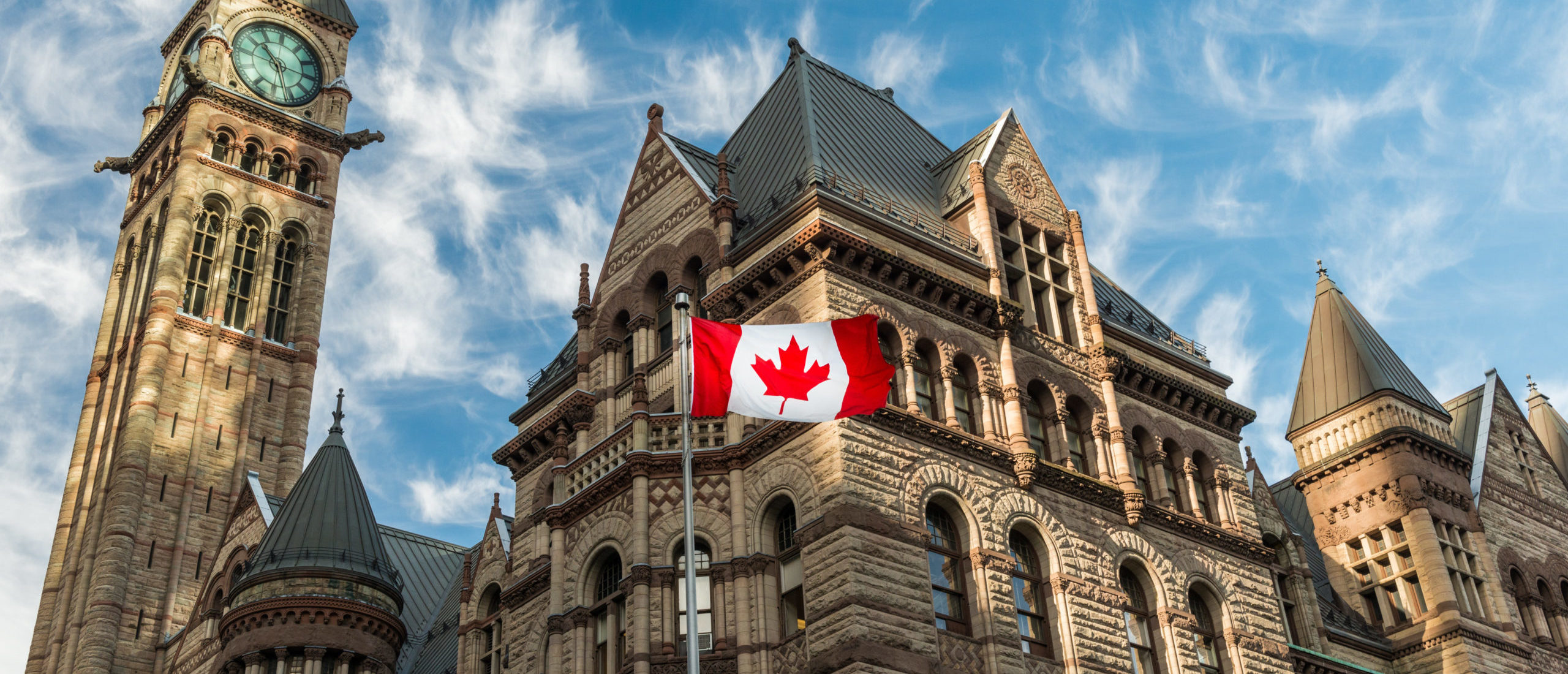 Canadian flag in front of Old City Hall in Toronto. By Joshua Davenport. Shutterstock.