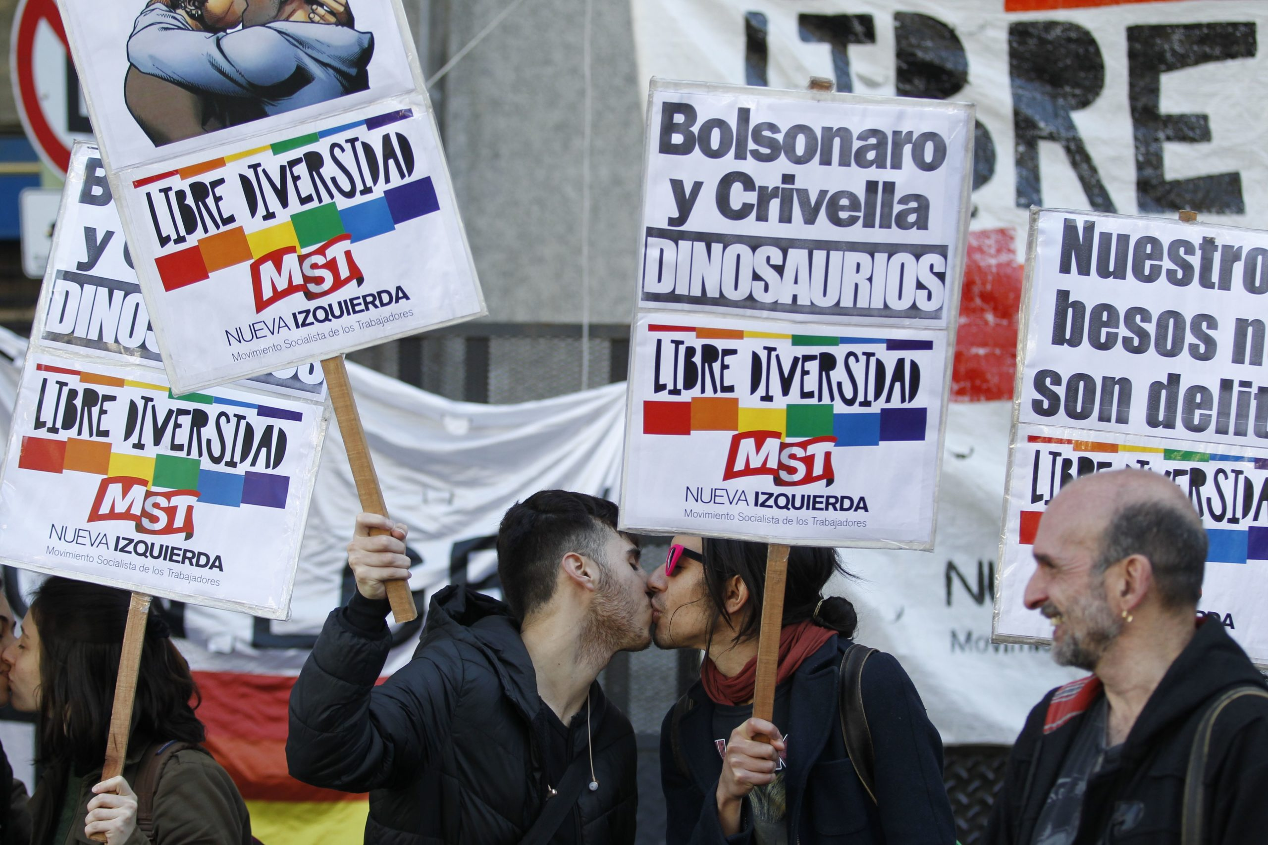 """Protestors kiss each other during a demonstration outside the Brazilian embassy in Buenos Aires on September 12, 2019, against Rio de Janeiro's mayor Marcelo Crivella, an Evangelical Protestant, after he ordered to remove a comic book from sale because of its """"sexual content for minors"""". - The comic that sparked the mayor's ire showed the Marvel superhero characters Wiccan and Hulkling exchanging a kiss, fully dressed. (Photo by Emiliano Lasalvia/AFP via Getty Images)"""