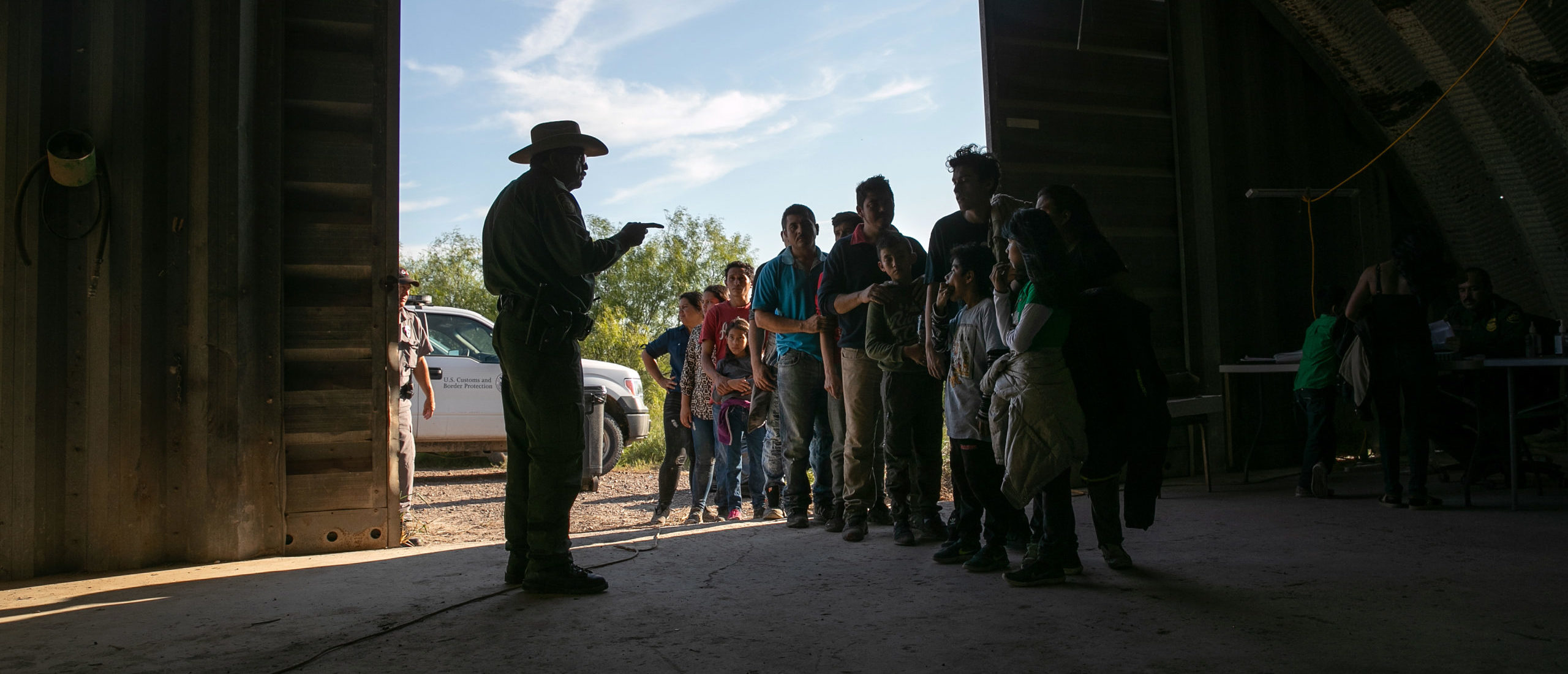 LOS EBANOS, TEXAS - SEPTEMBER 10: A U.S. Border Patrol agent gives instructions to families, mostly from Central America, who had crossed the Rio Grande from Mexico and presented themselves to agents on September 10, 2019 in Los Ebanos, Texas. Although the number of families seeking political asylum at the U.S. southern border has dropped in recent months, the number still far exceeds historic averages during summer months. (Photo by John Moore/Getty Images)