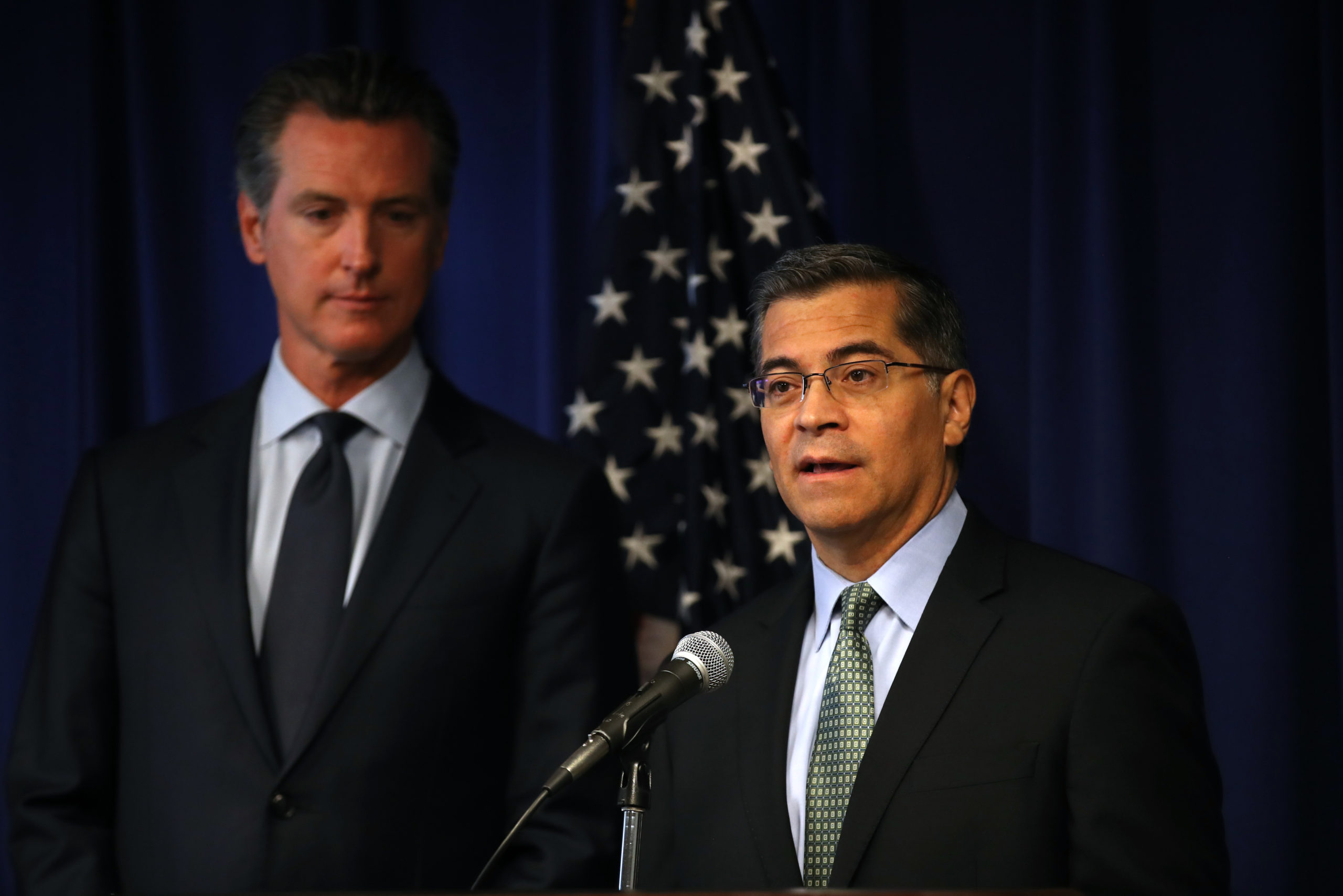 SACRAMENTO, CALIFORNIA - SEPTEMBER 18: California attorney general Xavier Becerra (R) speaks as California Gov. Gavin Newsom (L) looks on during a news conference at the California justice department on September 18, 2019 in Sacramento, California. California Gov. Gavin Newsom, California attorney general Xavier Becerra and California Air Resources Board Chair Mary Nichols held a news conference in response to the Trump Administration's plan to revoke California's waiver to establish vehicle emissions standards for greenhouse gas emissions and standards to require manufacturers to sell zero emissions vehicles. Under the federal Clean Air Act, California is allowed to set its own vehicle emissions standards that are at least as protective as the federal government's standards. The state has received 100 waivers from the Environmental Protection Agency (EPA) for higher standards than federally mandated over the past 50 years. (Justin Sullivan/Getty Images)