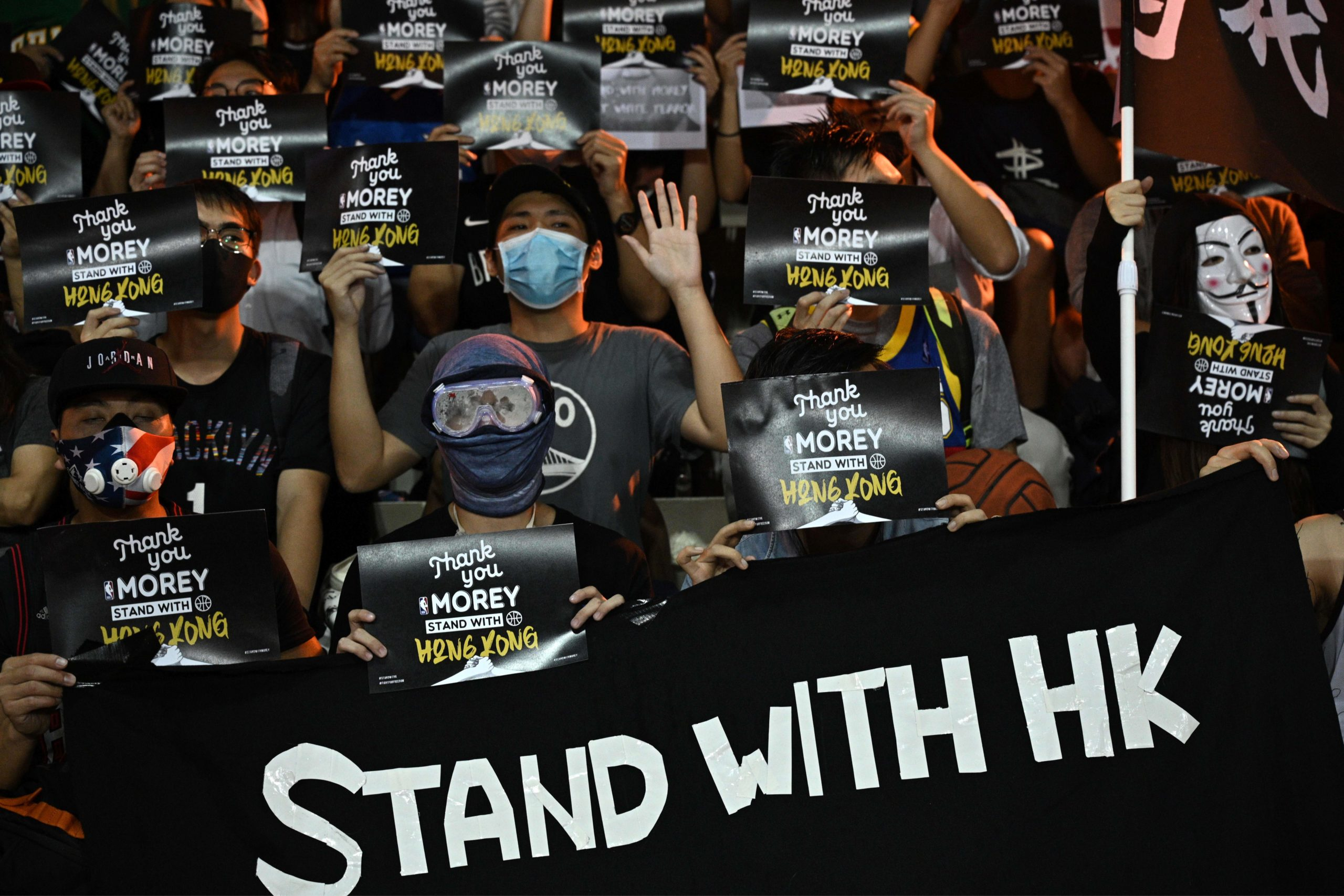 """Protesters shout slogans as they hold flyers at the Southorn Playground in Hong Kong on October 15, 2019, during a rally in support of NBA basketball Rockets general manager Daryl Morey and against comments made by Lakers superstar LeBron James. - US basketball superstar LeBron James on October 14, 2019, has sharply criticised a Houston Rockets executive for angering China with a tweet supporting protesters in Hong Kong, saying the executive was """"misinformed"""" and should have kept his mouth shut. (Photo by Anthony Wallace/AFP via Getty Images)"""