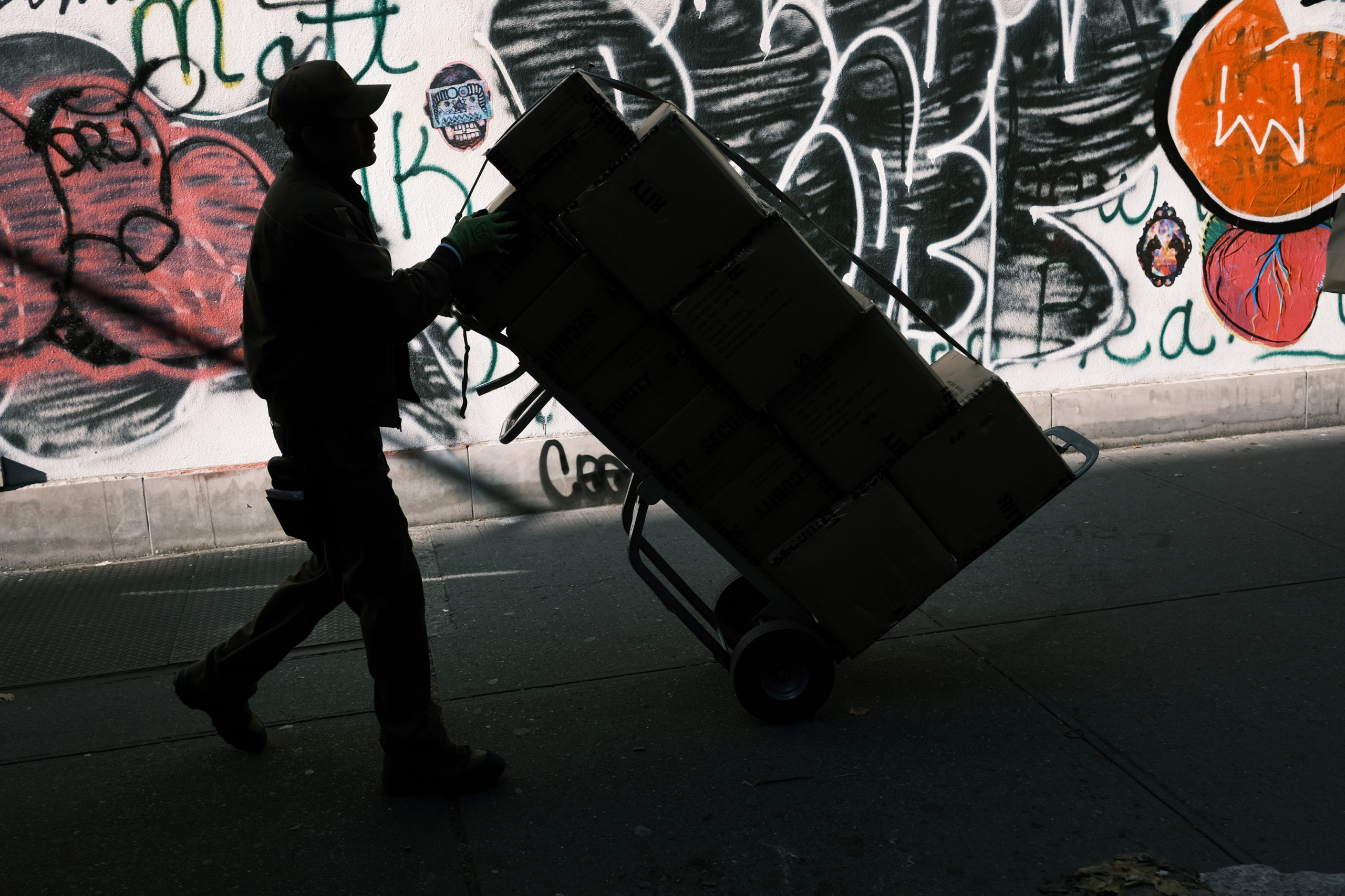NEW YORK, NEW YORK - NOVEMBER 21: A man moves a box on November 21, 2019 in New York City. As the internet increasingly becomes peoples preferred method for shopping, many cities and towns are witnessing an increase in trucks making deliveries. It is estimated that more than 1.5million packages are delivered to New York City every day, causing truck gridlock, pollution and increased danger to cyclists and pedestrians. (Photo by Spencer Platt/Getty Images)