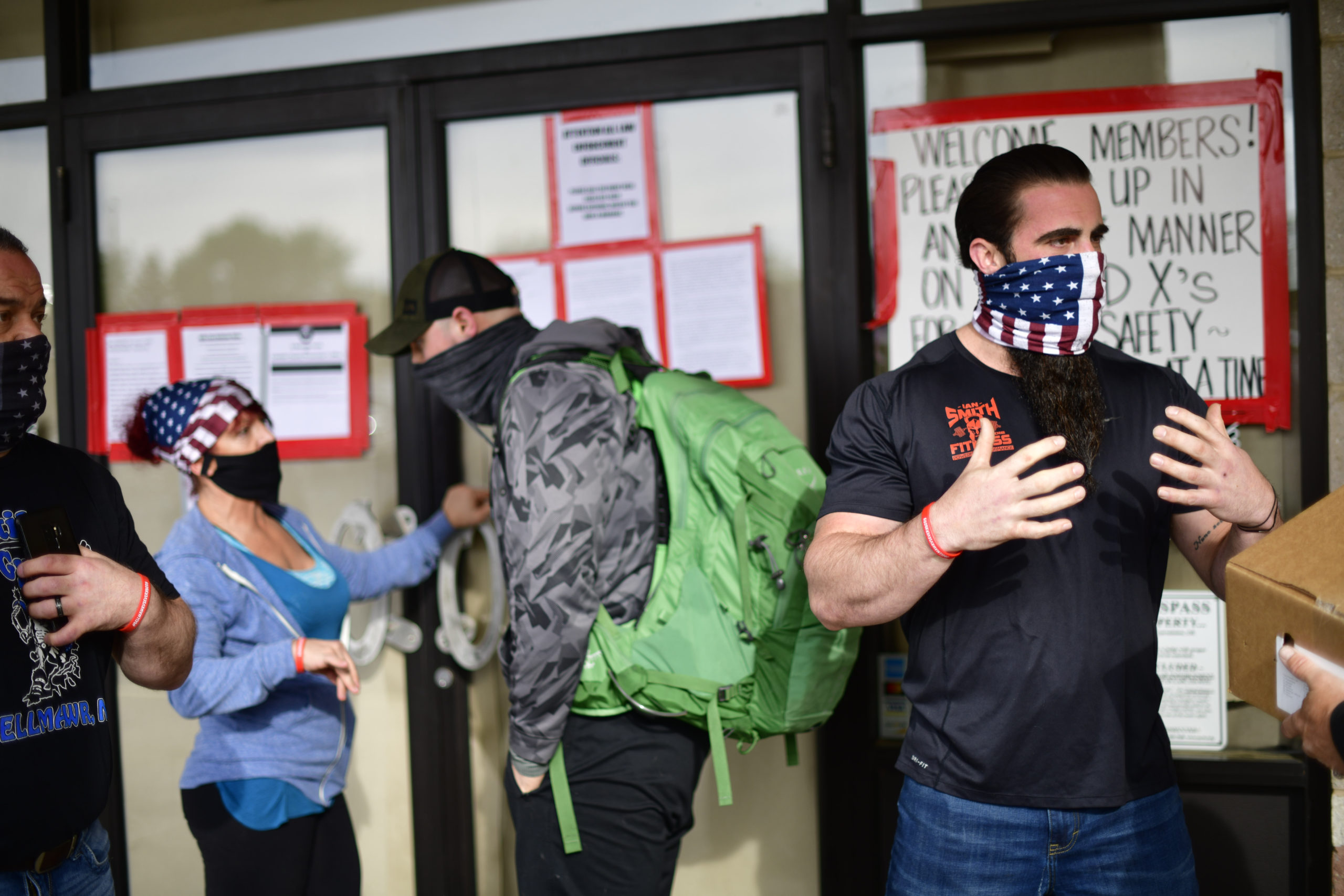 BELLMAWR, NJ - MAY 20: Employees confer with patrons lining up outside the Atilis Gym on May 20, 2020 in Bellmawr, New Jersey. The gym has opened for the third consecutive day, defying the New Jersey Governor's mandate that many retail businesses stay closed due to the coronavirus pandemic. (Mark Makela/Getty Images)