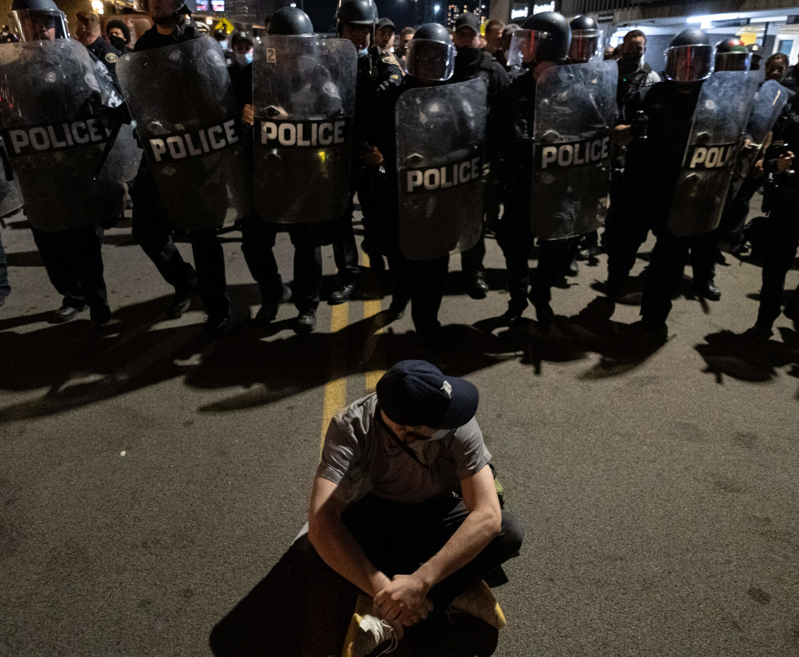 A protester kneels with his back to the US riot police in the city of Detroit, Michigan, on May 29, 2020, over the death of George Floyd, a black man who died after a white policeman knelt on his neck for several minutes. - Violent protests erupted across the United States late on May 29, over the death of a handcuffed black man in police custody, with murder charges laid against the arresting Minneapolis officer failing to quell boiling anger. (SETH HERALD/AFP via Getty Images)