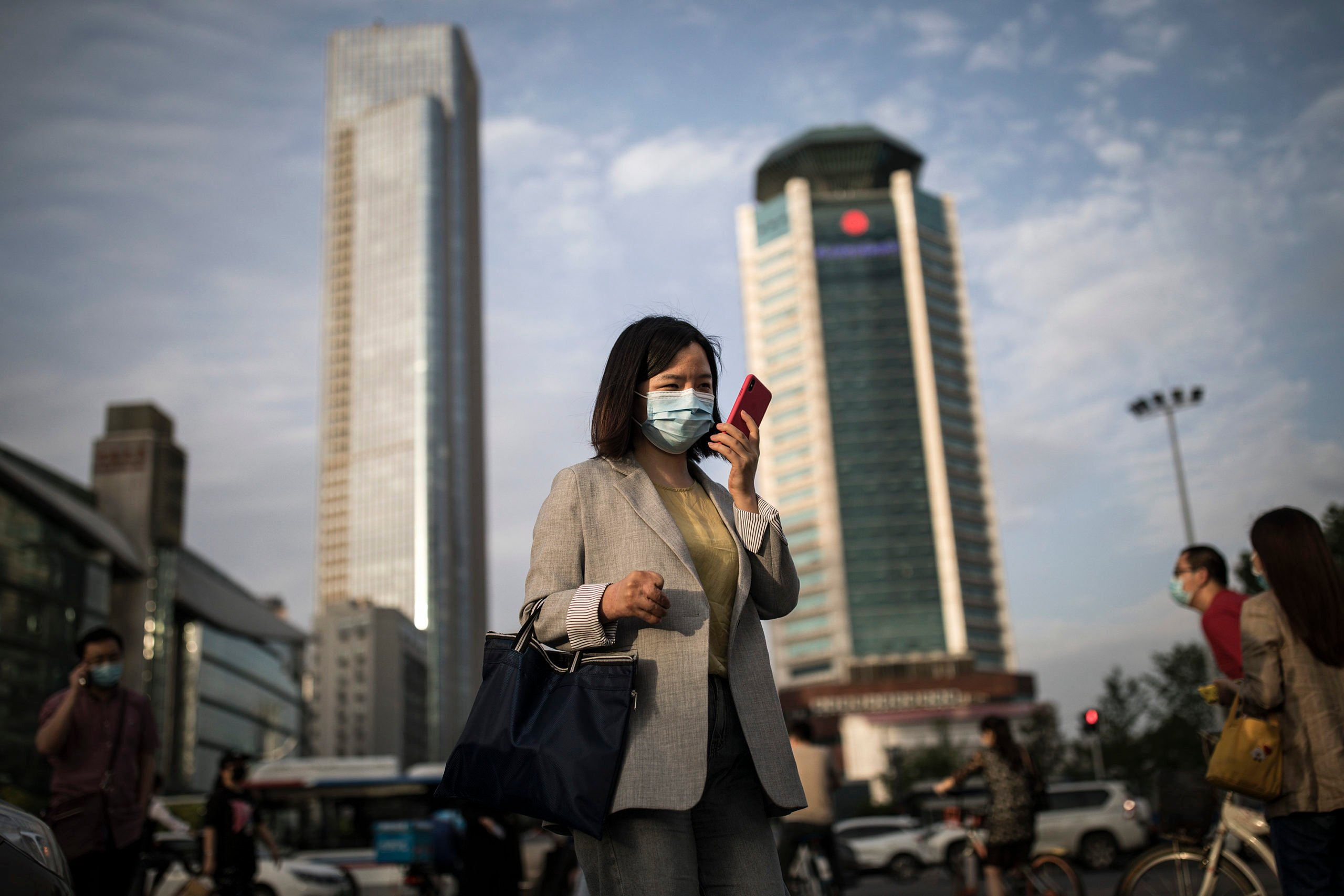 WUHAN, CHINA - MAY 11: (CHINA OUT) A women wears a mask while uses iPhone pass the crossroads on May 11, 2020 in Wuhan, China. The government has begun lifting outbound travel restrictions after almost 11 weeks of lockdown to stem the spread of COVID-19. (Photo by Getty Images)