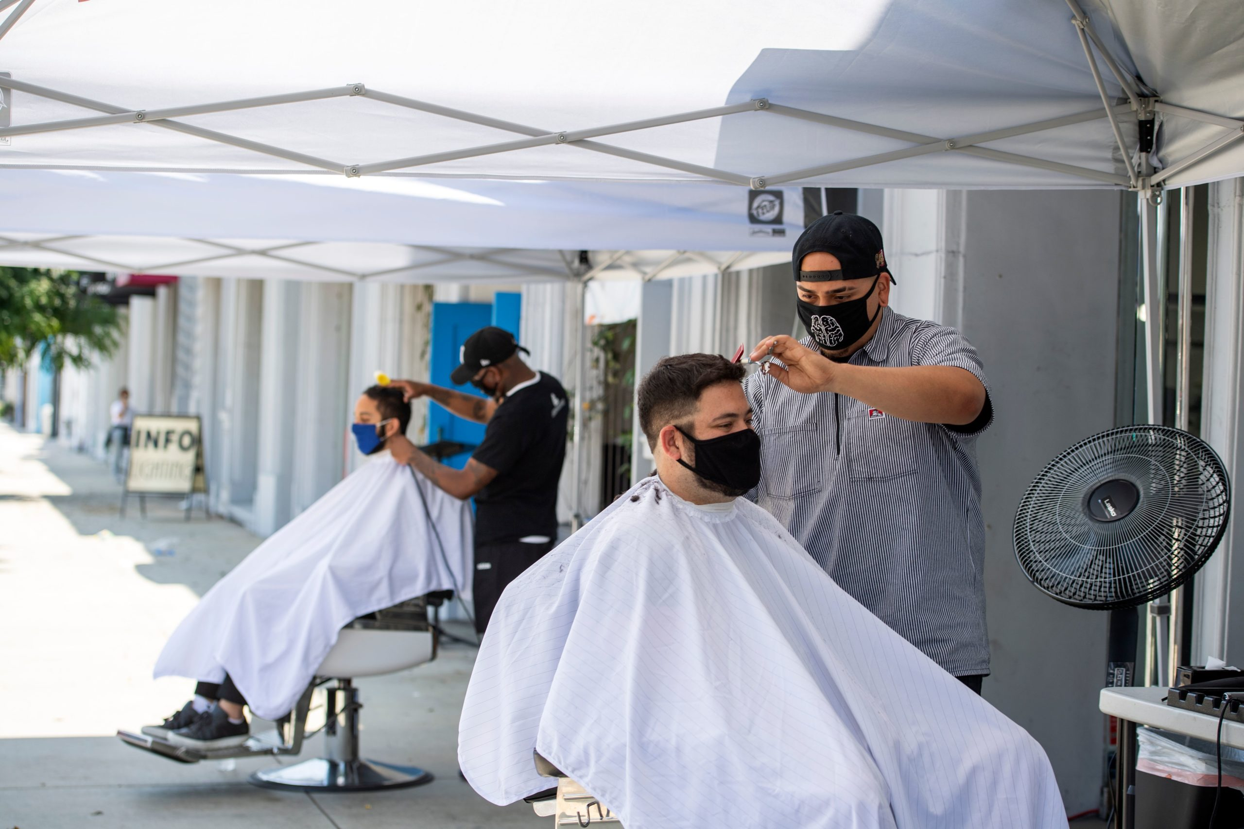 Stylists from a Los Angeles, California barbershop cut clients' hair on Aug. 4. (Valerie Macon/AFP via Getty Images)