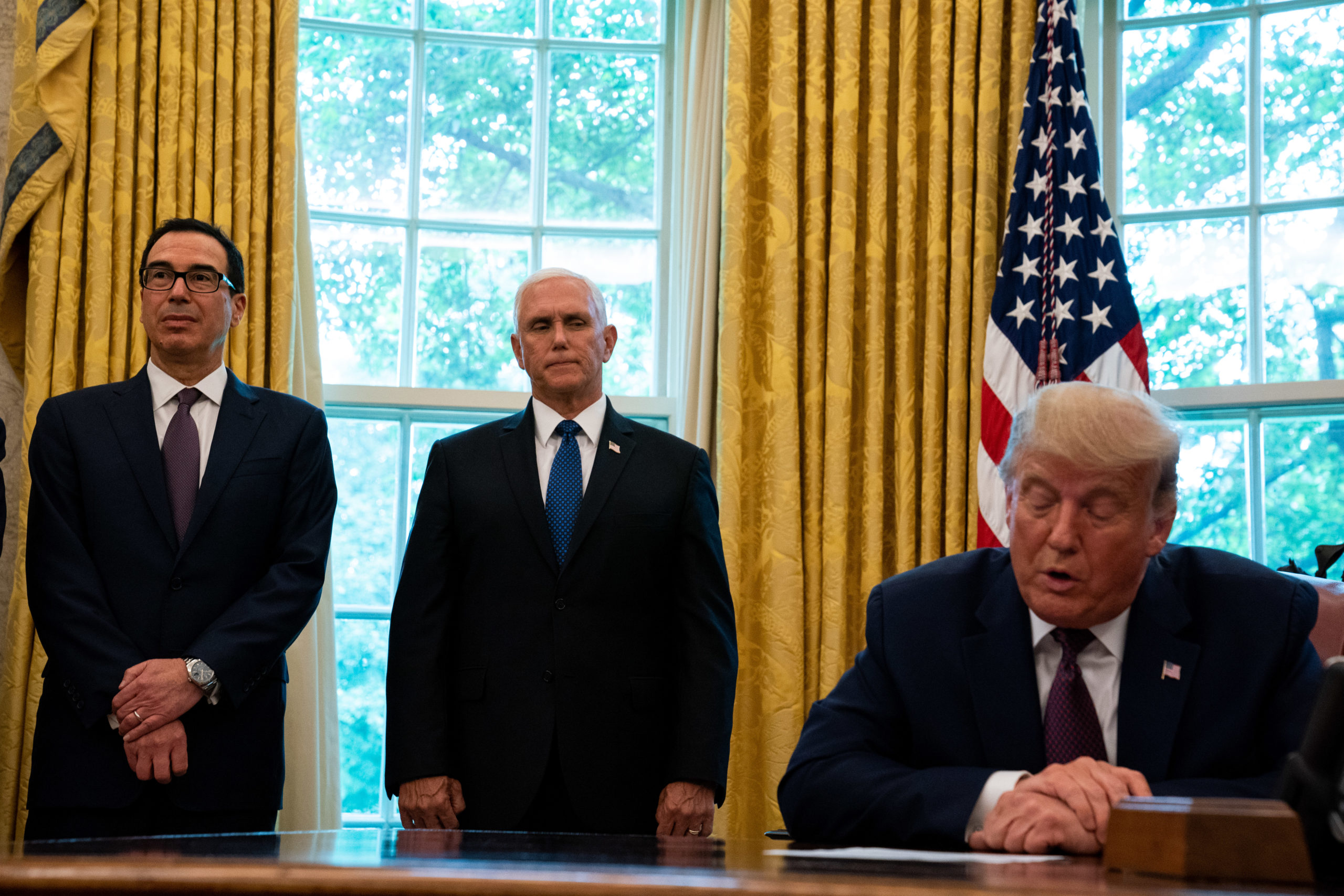 WASHINGTON, DC - SEPTEMBER 11: U.S. President Donald Trump, flanked by U.S. Treasury Secretary Steven Mnuchin (L) and U.S. Vice President Mike Pence (C), speaks in the Oval Office to announce that Bahrain will establish diplomatic relations with Israel, at the White House in Washington, DC on September 11, 2020. The announcement follows one last month by Israel and the United Arab Emirates that they would seek to normalize relations with each other. (Photo by Anna Moneymaker-Pool/Getty Images)