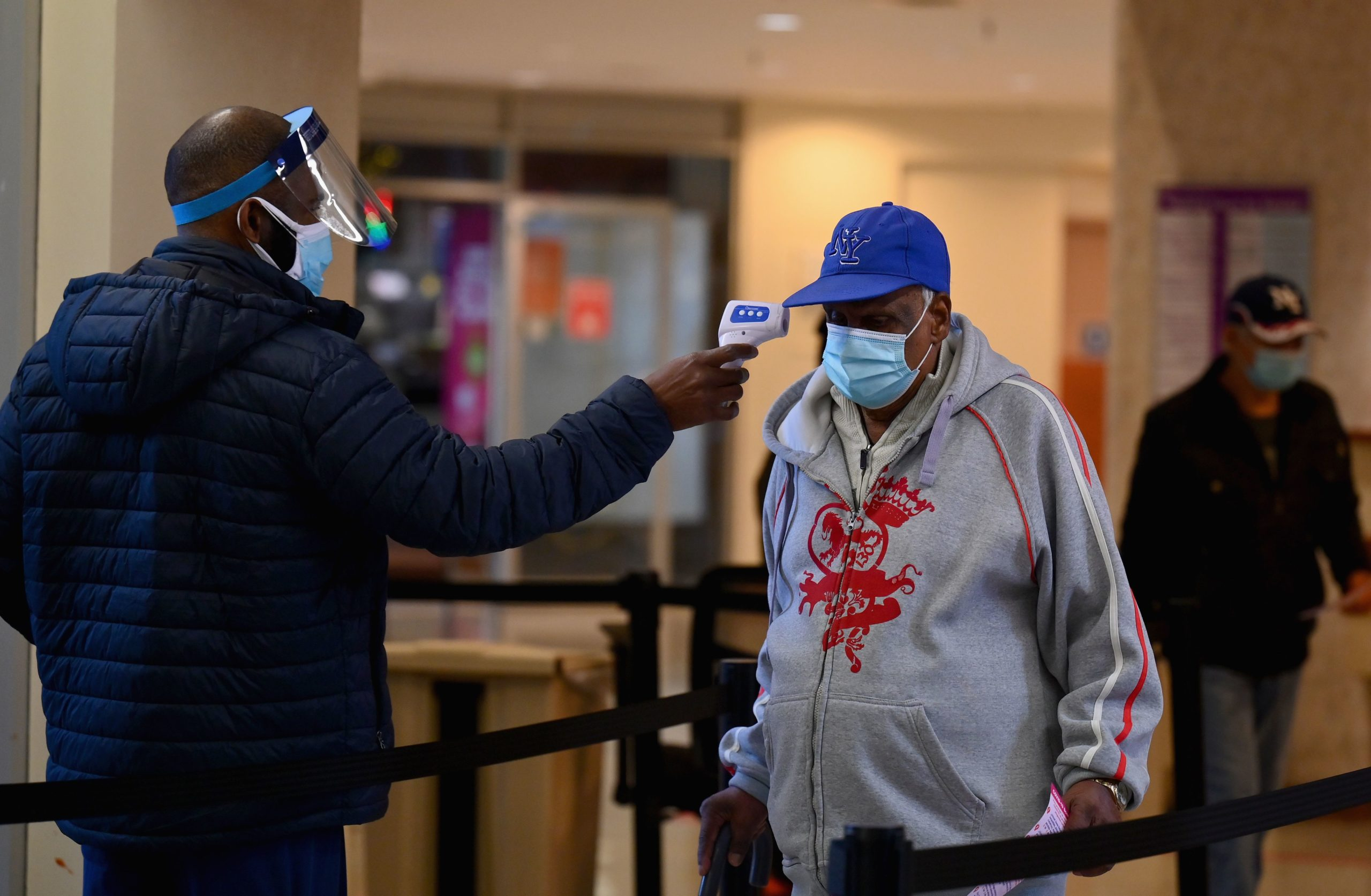 A staff member checks the temperature of a visitor at Woodhull Medical and Mental Health Center on Dec. 1 in New York City. (Angela Weiss/AFP via Getty Images)