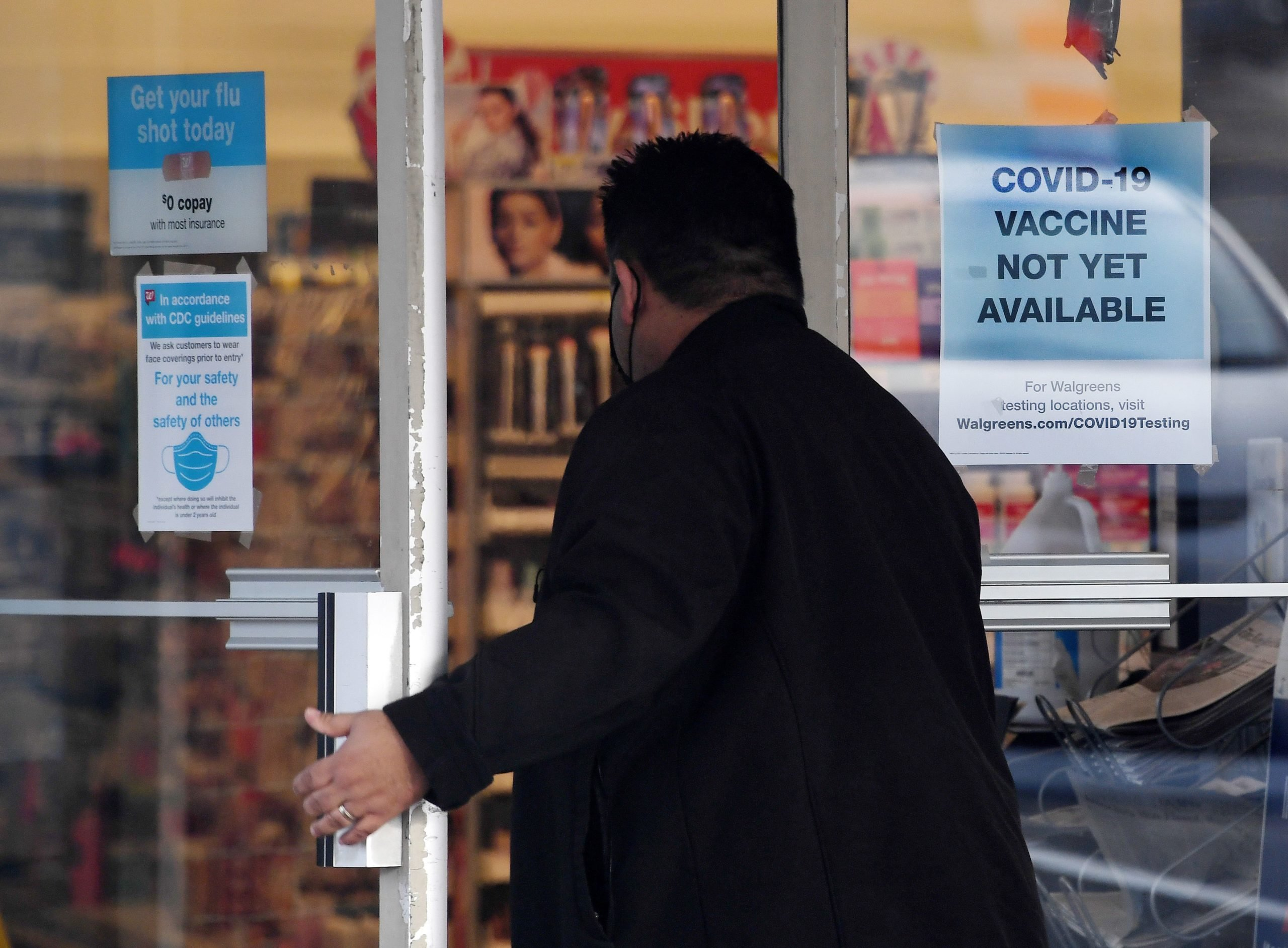 "A man walks into a store with a ""Covid-19 vaccine not yet available"" sign in Arlington, Virginia on Dec. 1. (Olivier Douliery/AFP via Getty Images)"