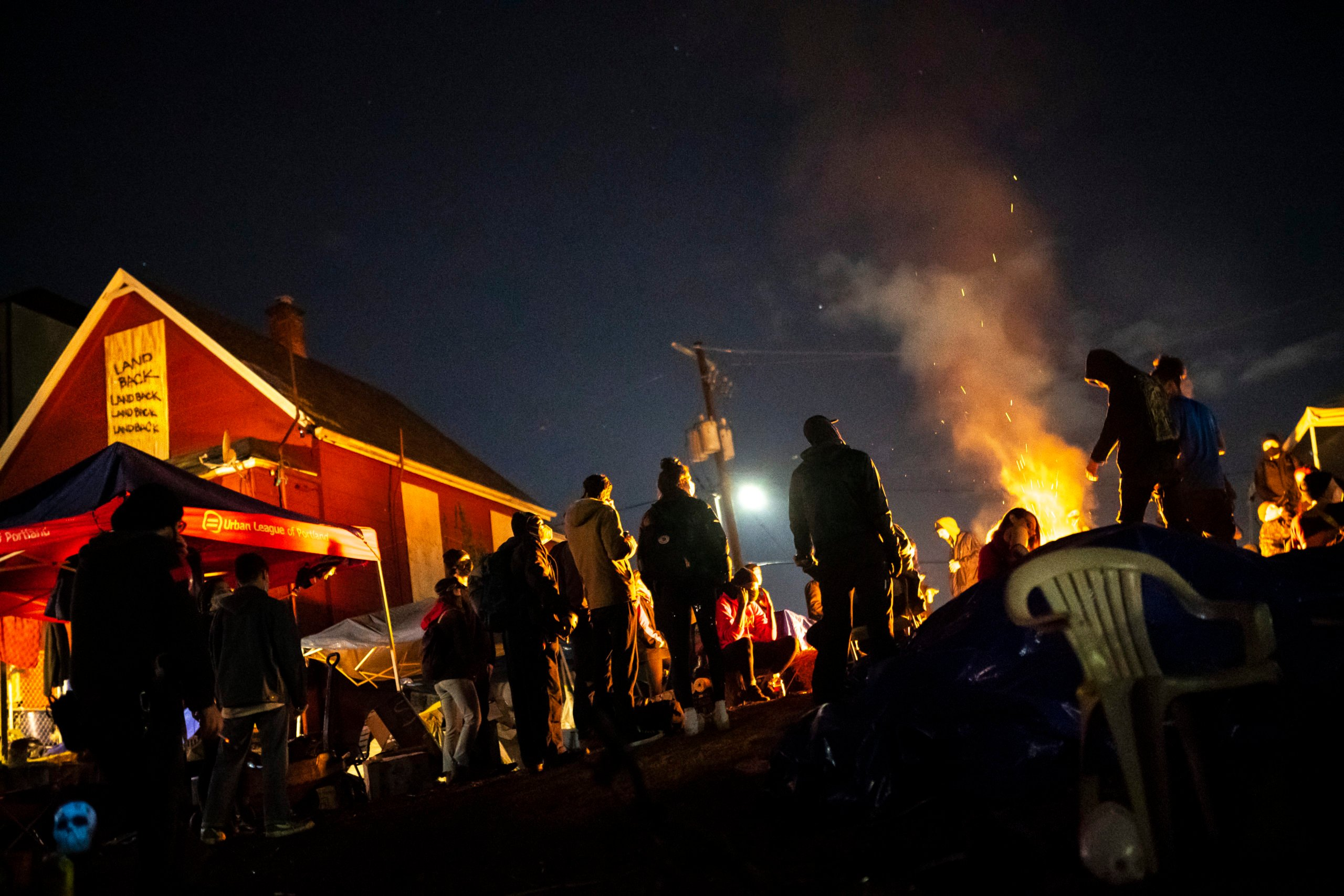 Protesters plan their next action while standing around a fire near the Red House on Mississippi Street on December 9, 2020 in Portland, Oregon. (Nathan Howard/Getty Images)