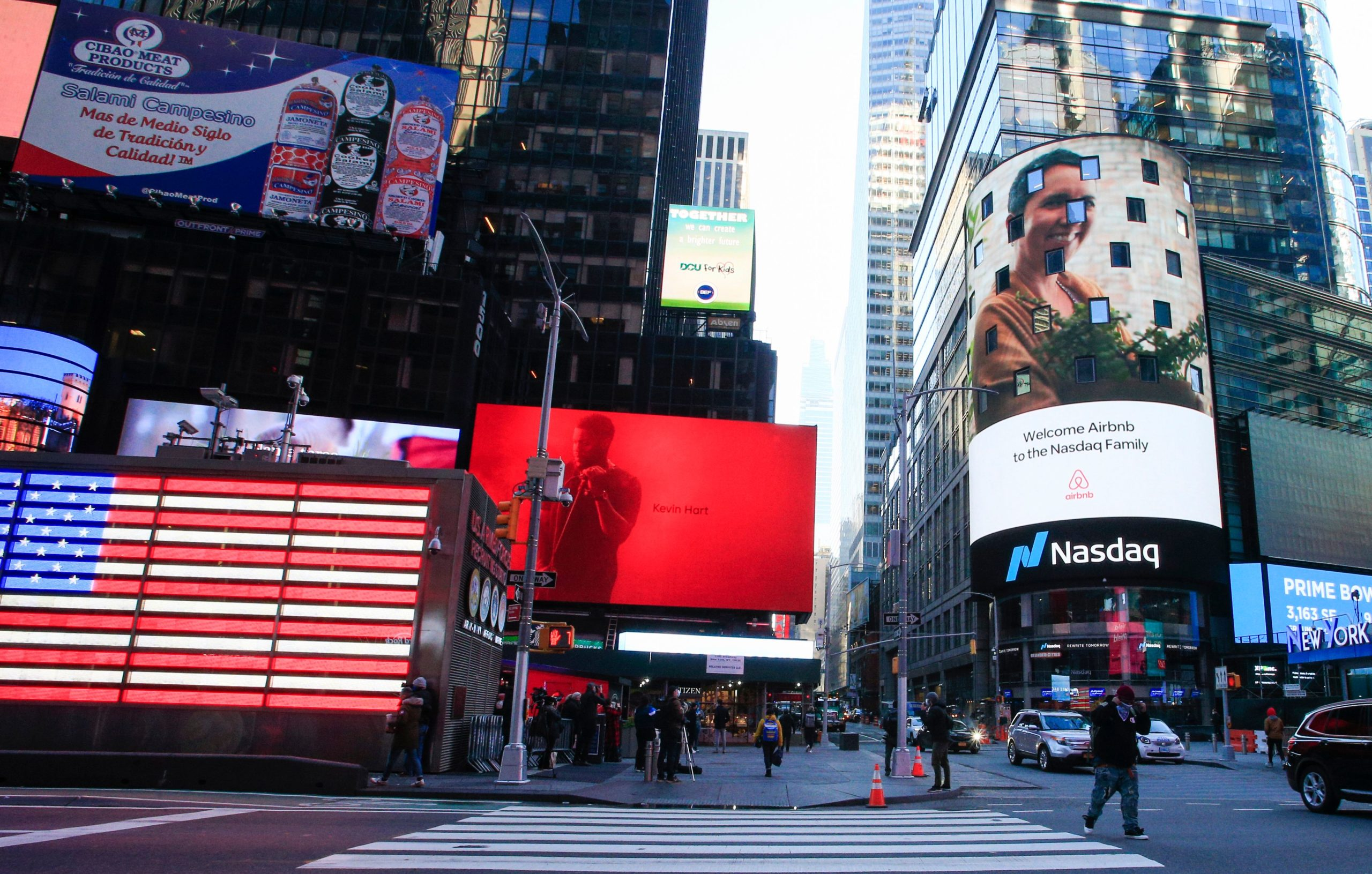 The Airbnb logo (R) is displayed on the Nasdaq digital billboard in Times Square in New York on December 10, 2020. - Home-sharing giant Airbnb was set for its Wall Street debut Thursday with a whopping $47 billion valuation amid a feverish rush for new shares in companies adapting to lifestyle changes imposed by the coronavirus pandemic. (Photo by Kena Betancur / AFP) (Photo by KENA BETANCUR/AFP via Getty Images)
