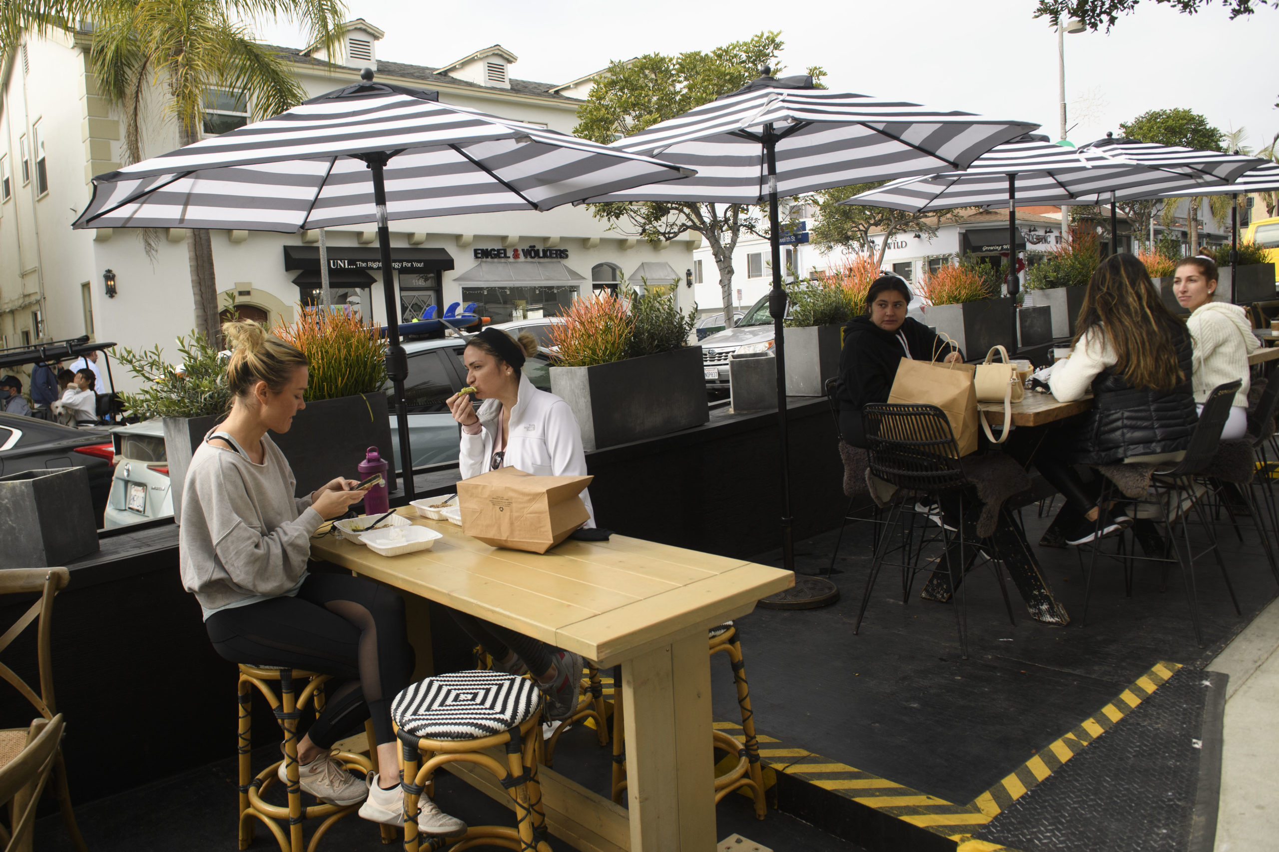 """People eat take-out food outdoors at a """"public parklet"""" due to Covid-19 restrictions on restaurant outdoor dining in Manhattan Beach, California, December 12, 2020. - According to California health officials, ICU bed capacity in the Southern California region has dropped to 5.3% as more restrictive orders are imposed to prevent hospitals from being overrun. (Photo by Patrick T. Fallon / AFP) (Photo by PATRICK T. FALLON/AFP via Getty Images)"""