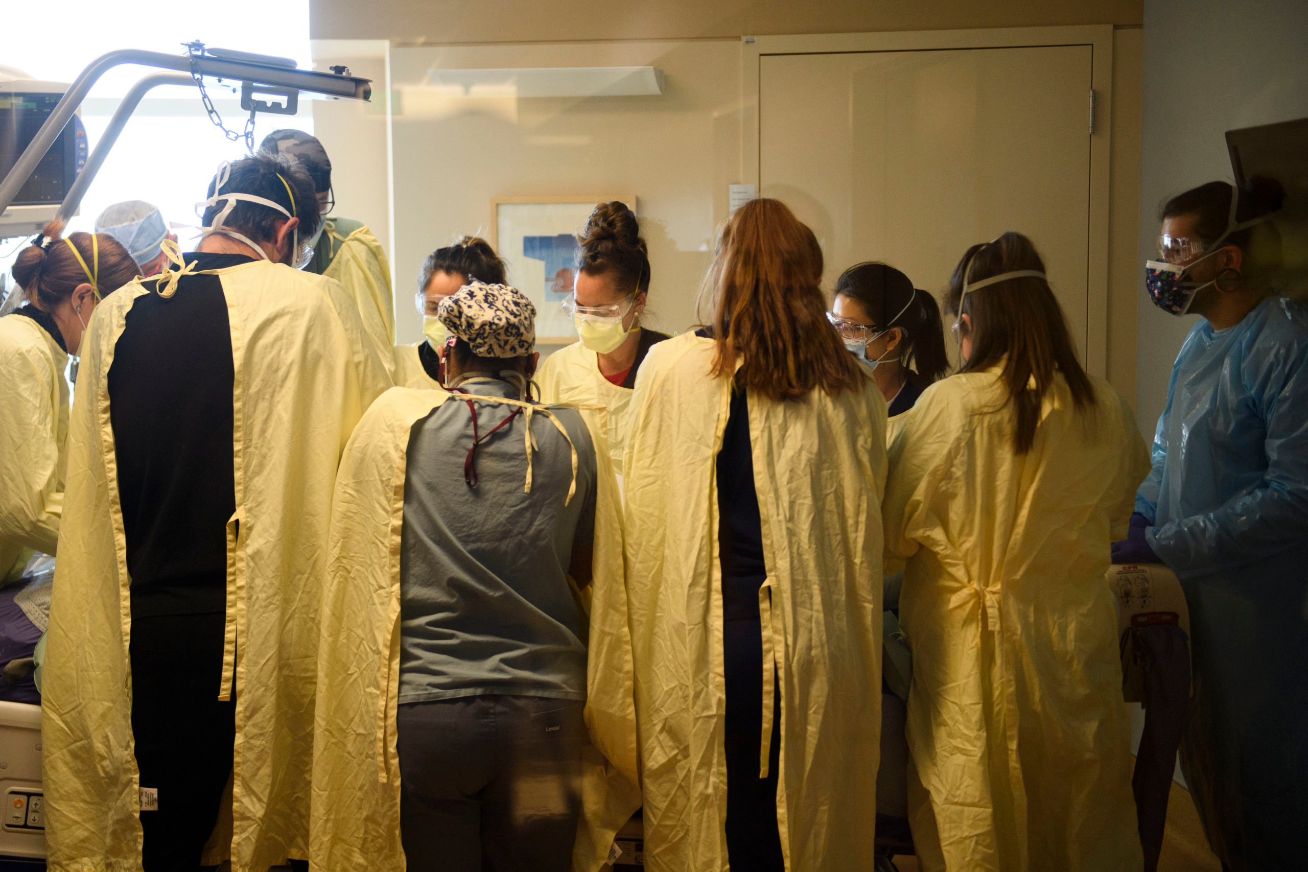"""A team of health care workers including physicians, nurses, certified nursing assistants, and respiratory specialists wear personal protective equipment (PPE) while turning a patient from their stomach onto their back in the Covid-19 intensive care unit (ICU) at Renown Regional Medical Center on December 16, 2020 in Reno, Nevada. - Renown Health converted two floors of a parking garage into an alternative care site for Covid-19 patients to increase hospital capacity amid a surge in cases, allowing other facilities to be used for patients in more serious condition. The site included the addition of flooring, electrical infrastructure, lighting, water, technology, sanitation, and ventilation. President Trump earlier this month retweeted a tweet that described Renown's structure as """"the fake Nevada parking garage hospital"""" due to a lack of patients in the picture taken before the facility opened. The site is for patients that have mild to moderate Covid-19 cases and do not require critical care, with 24 patients currently and 350 patient visits to date. (Photo by Patrick T. Fallon / AFP) (Photo by PATRICK T. FALLON/AFP via Getty Images)"""
