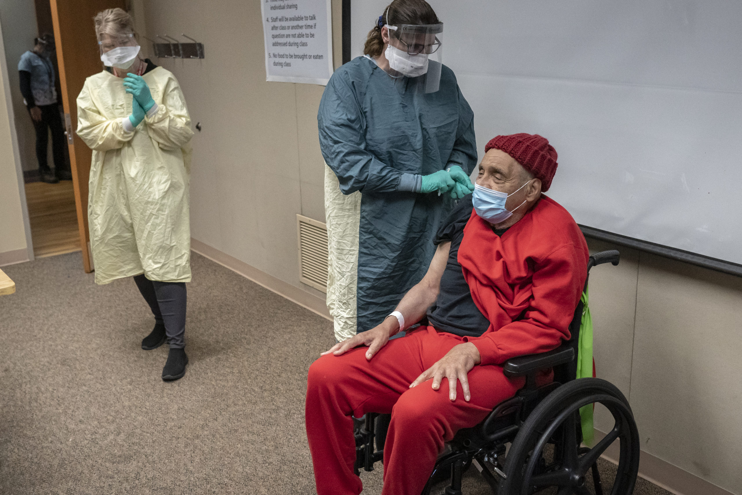 Medical staff applaud as Vietnam War Army veteran James Curry, 78, receives a coronavirus vaccination at a Veterans Affairs long-term care facility on Thursday in Washington. (Nathan Howard/Getty Images)