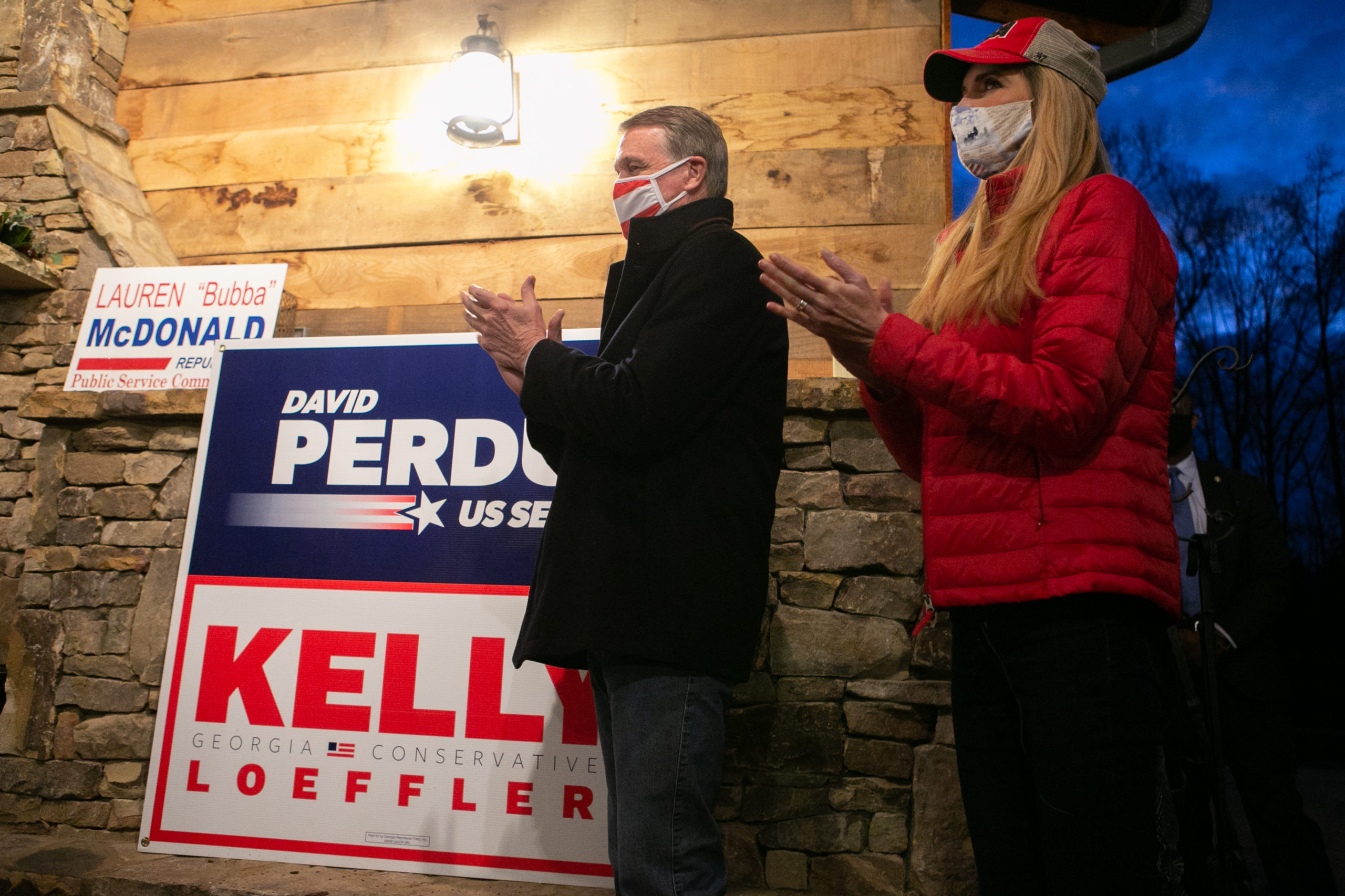 CUMMING, GA - DECEMBER 20: Georgia Republican Senate candidates David Perdue (R-GA) and Kelly Loeffler (R-GA) listen to former U.N. Ambassador Nikki Haley speak during a rally on December 20, 2020 in Cumming, Georgia. The Senate Firewall campaign event comes ahead of a crucial runoff election for Perdue and Loeffler on January 5th that will determine what party controls the United States Senate. (Photo by Jessica McGowan/Getty Images)