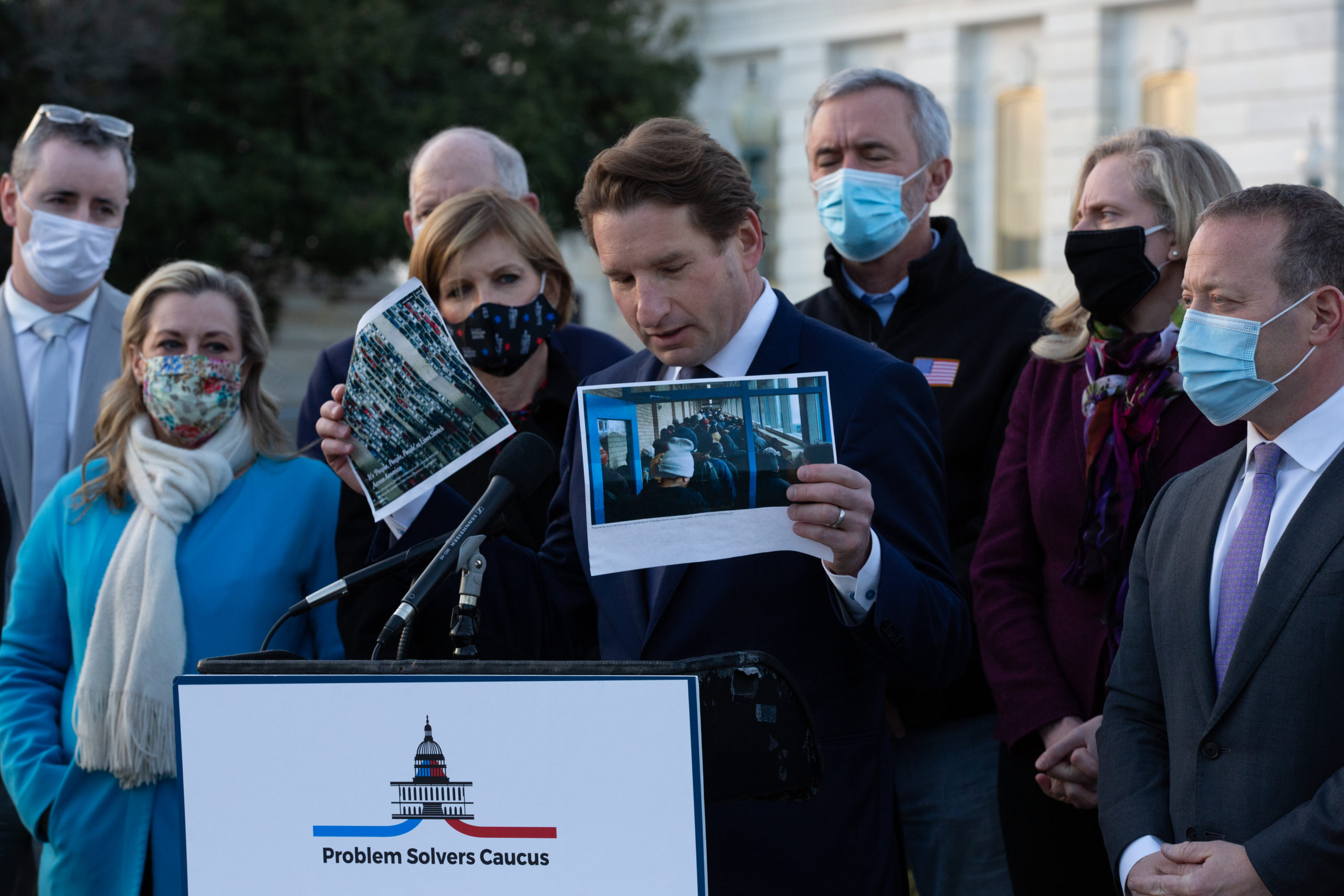 Rep. Dean Phillips holds up images of people in food bank lines, standing with members of the Problem Solvers Caucus at a Monday press conference to praise the forthcoming passage of the bipartisan emergency coronavirus relief bill. (Cheriss May/Getty Images)